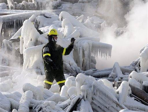 A police investigator signals to colleagues as they search through icy rubble to trying to locate more victims of a fire that destroyed a seniors' residence Friday, Jan. 24, 2014, in L'Isle-Verte, Quebec. Five people are confirmed dead and 30 people are still missing, while with cause of Thursday morning's blaze is unclear police said. Authorities are using steam to melt the ice and to preserve any bodies that are buried.