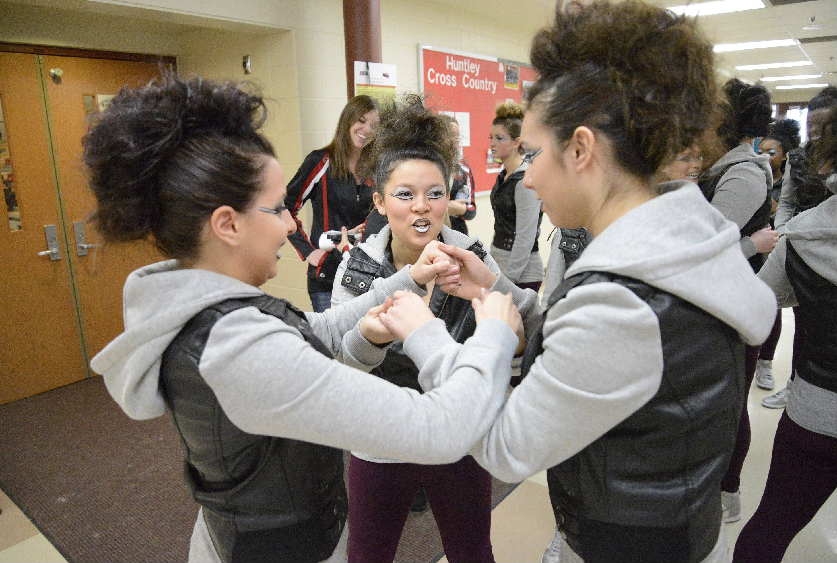 Huntley High School's Victoria Oliveira, 18, left, Tiffany Quinones, 15, center, and Melanie Naranjo, 16, huddle for a group handshake before their performance at the IHSA 3A competitive dance sectionals at Huntley High School on Saturday.