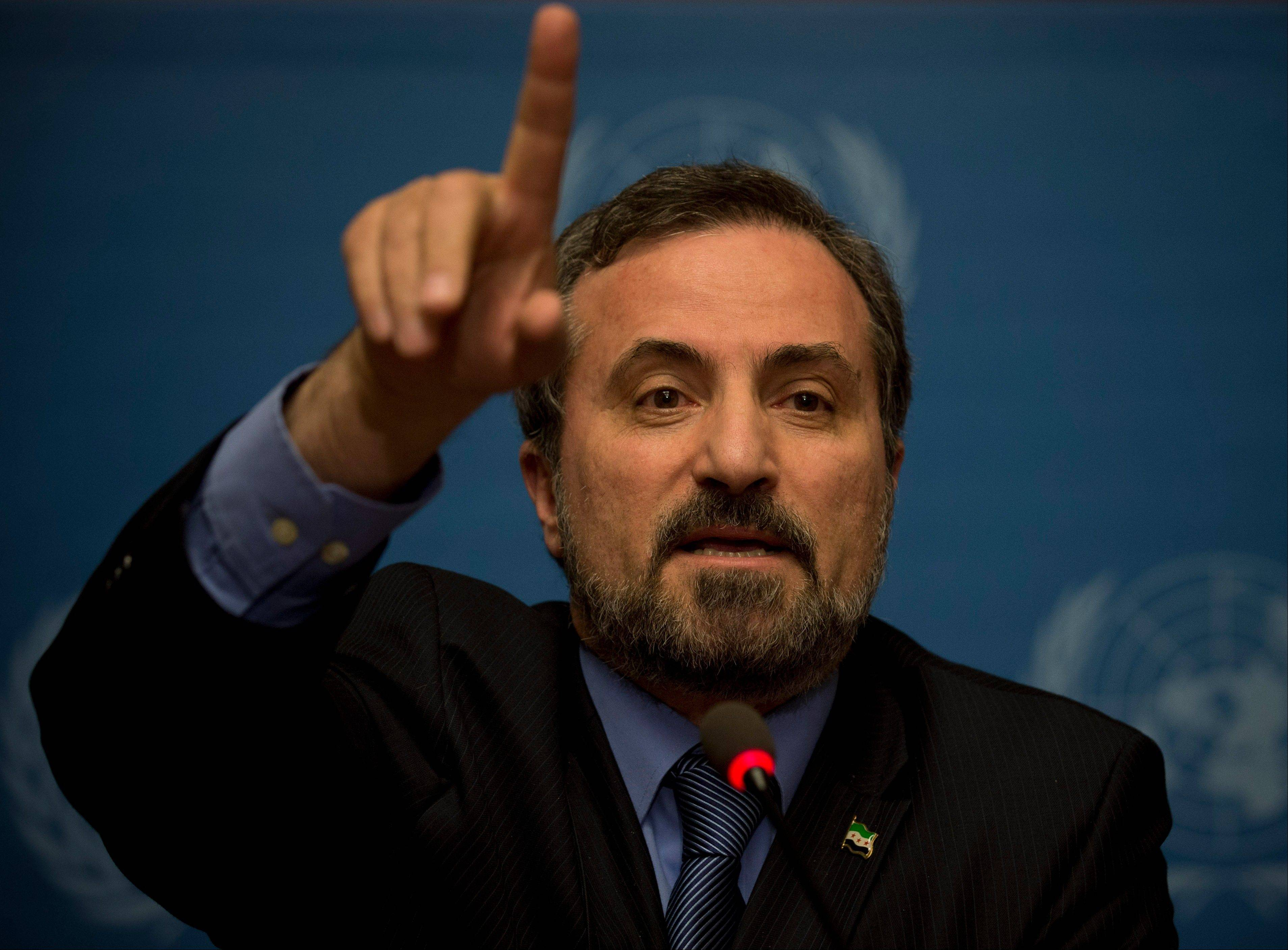 Louay Safi, spokesperson for the Syrian National Coalition, Syria's main political opposition group, gestures Saturday as he speaks to journalists at the United Nations headquarters in Geneva, Switzerland.