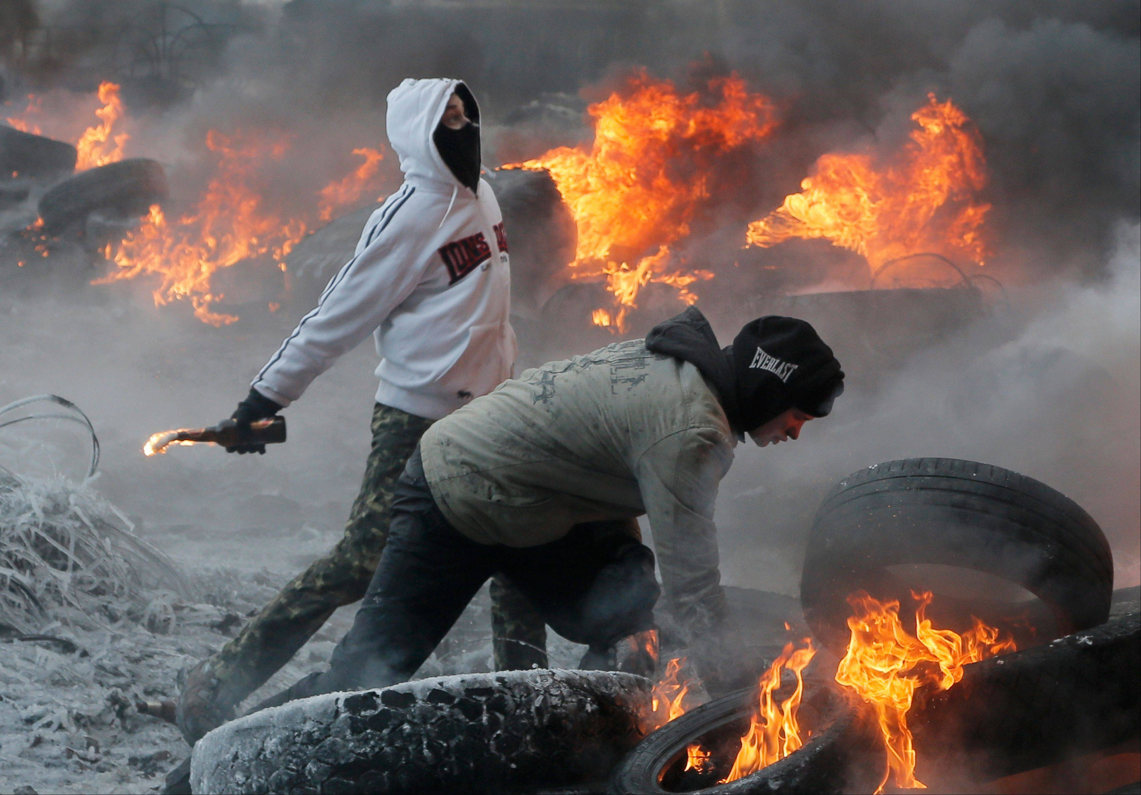 Protesters throw Molotov cocktails at riot police Saturday during a clash in central Kiev, Ukraine.