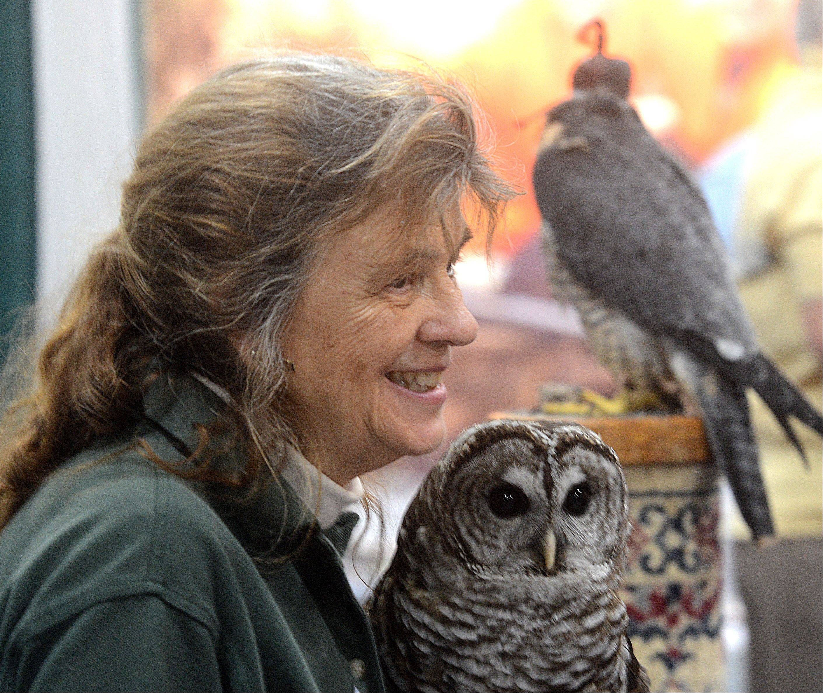 Barbara Schmidt, co-founder of The Northern Illinois Raptor Center, speaks to visitors about the barred owl she is holding during the Chicagoland Fishing Travel & Outdoor Expo at Renaissance Schaumburg Hotel and Convention Center. Behind her is a peregrine falcon.