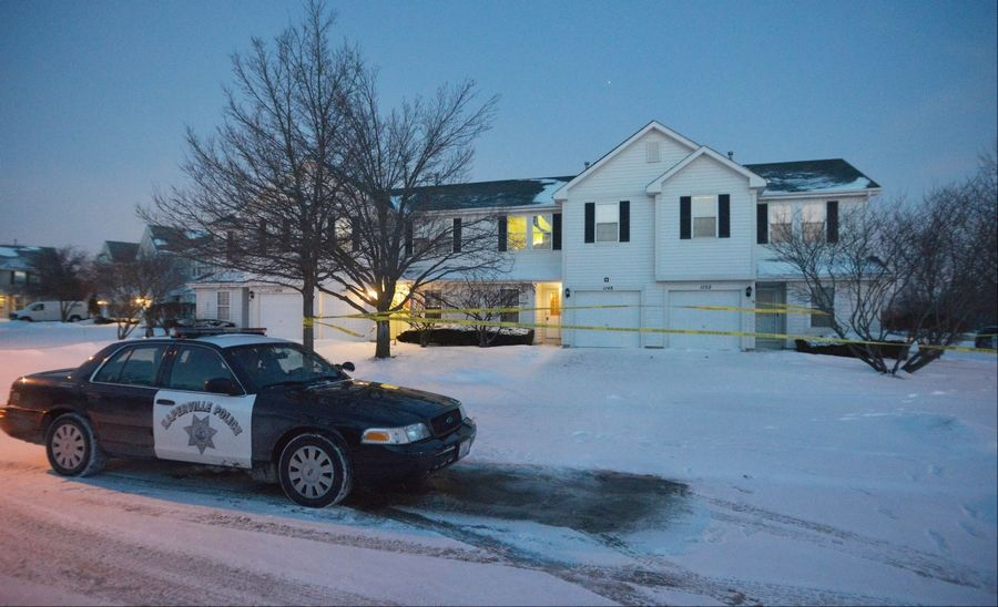 A Naperville police car idles in front of a two-story townhouse on Vail Court in Naperville early Wednesday evening after 54-year-old Charles Clark was found murdered inside.