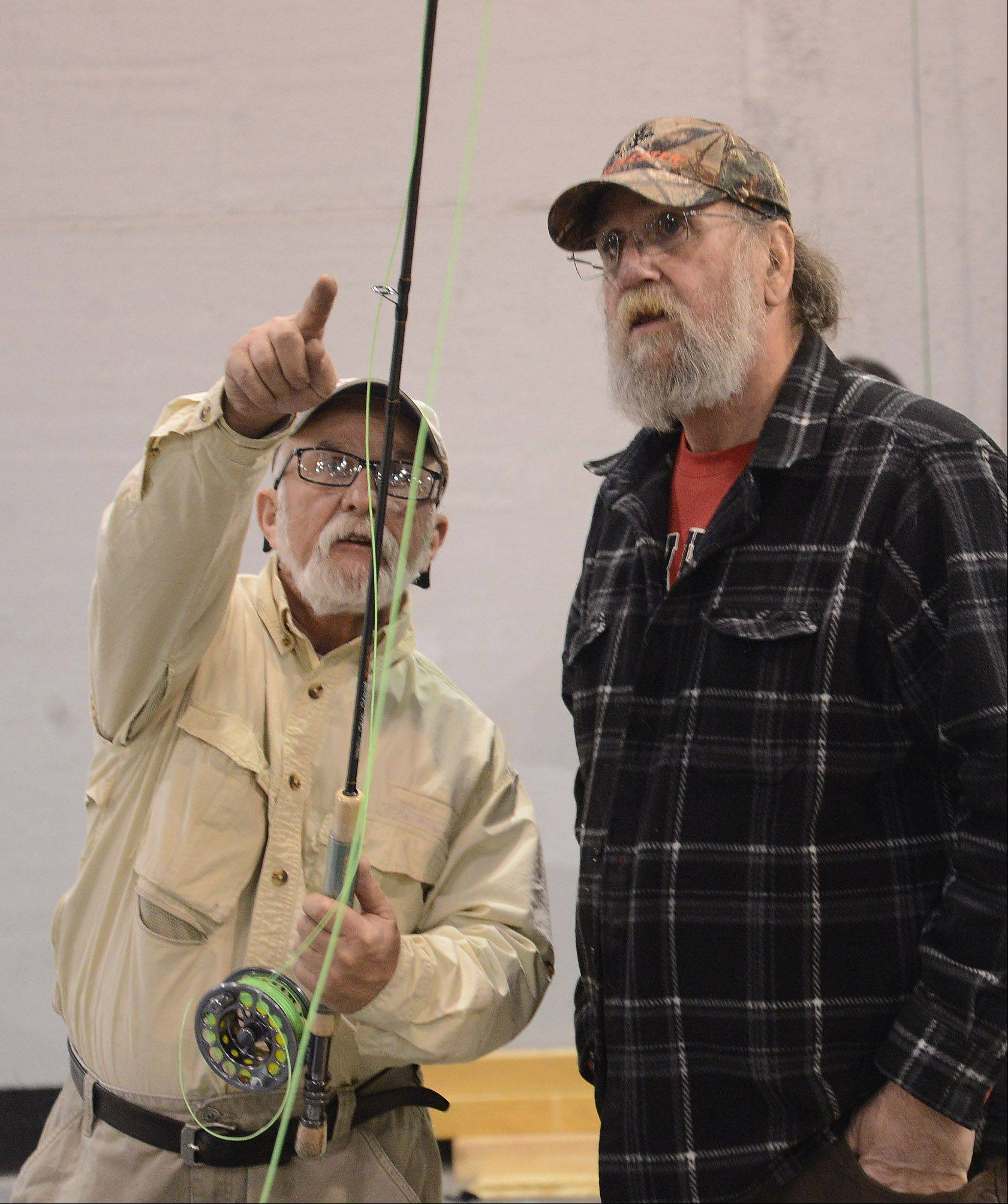 Captain Mike Corblies of American Fly Fishing Schools, left, gives a lesson in fly fishing Friday to Andy Tory of Evergreen Park, at the 28th Annual Chicago Outdoor Sports Show at the Donald E. Stephens Convention Center in Rosemont.