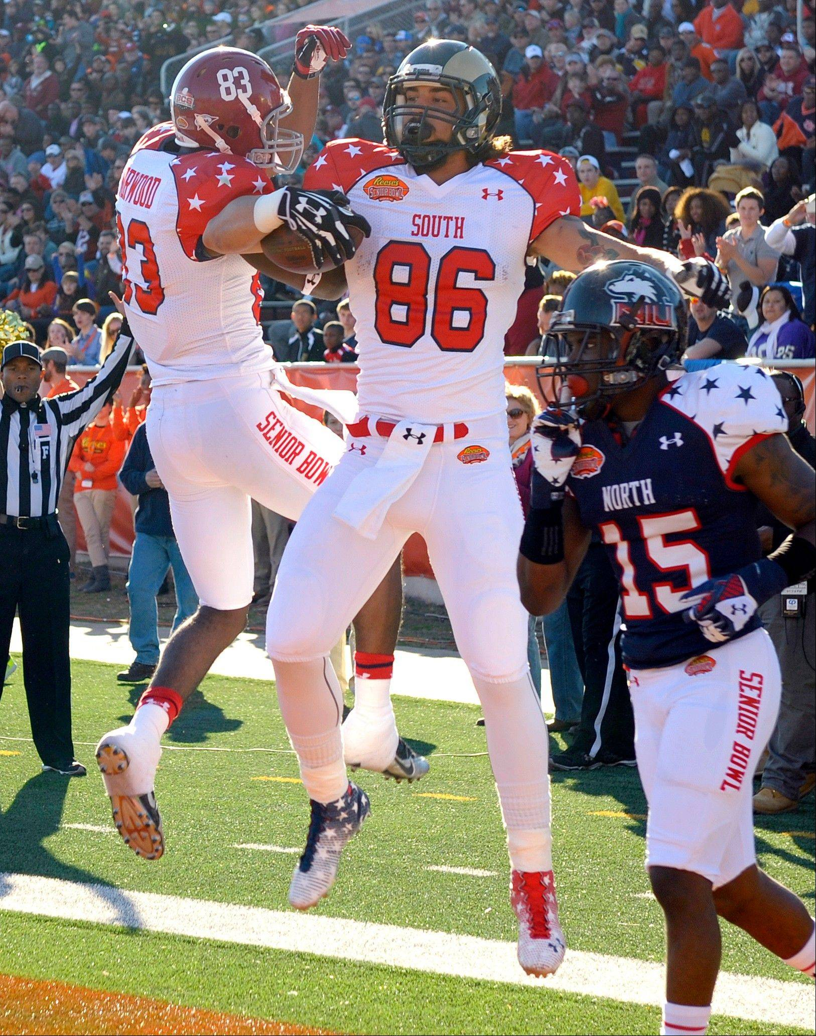 South wide receiver Kevin Norwood (83), of Alabama, celebrates with tight end Crockett Gilmore (86), of Colorado State, following Gilmore's touchdown catch during the first quarter of the Senior Bowl NCAA college football game on Saturday, Jan. 25, 2014, in Mobile, Ala. At right is North safety Jimmie Ward (15), of Northern Illinois.