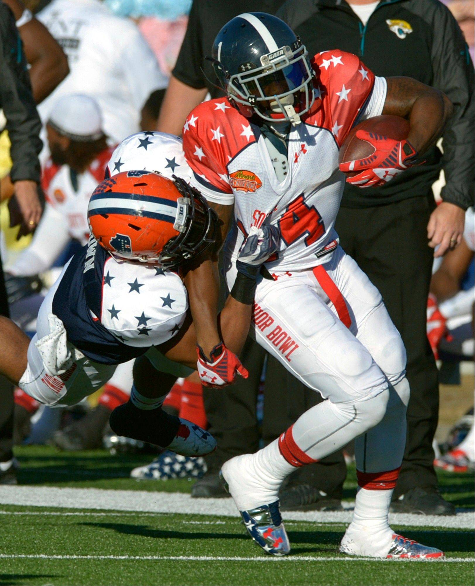 North outside linebacker Jonathan Brown, left, of Illinois, tackles South running back Jerick McKinnon, of Georgia Southern, during the second quarter of the Senior Bowl NCAA college football game on Saturday, Jan. 25, 2014, in Mobile, Ala.
