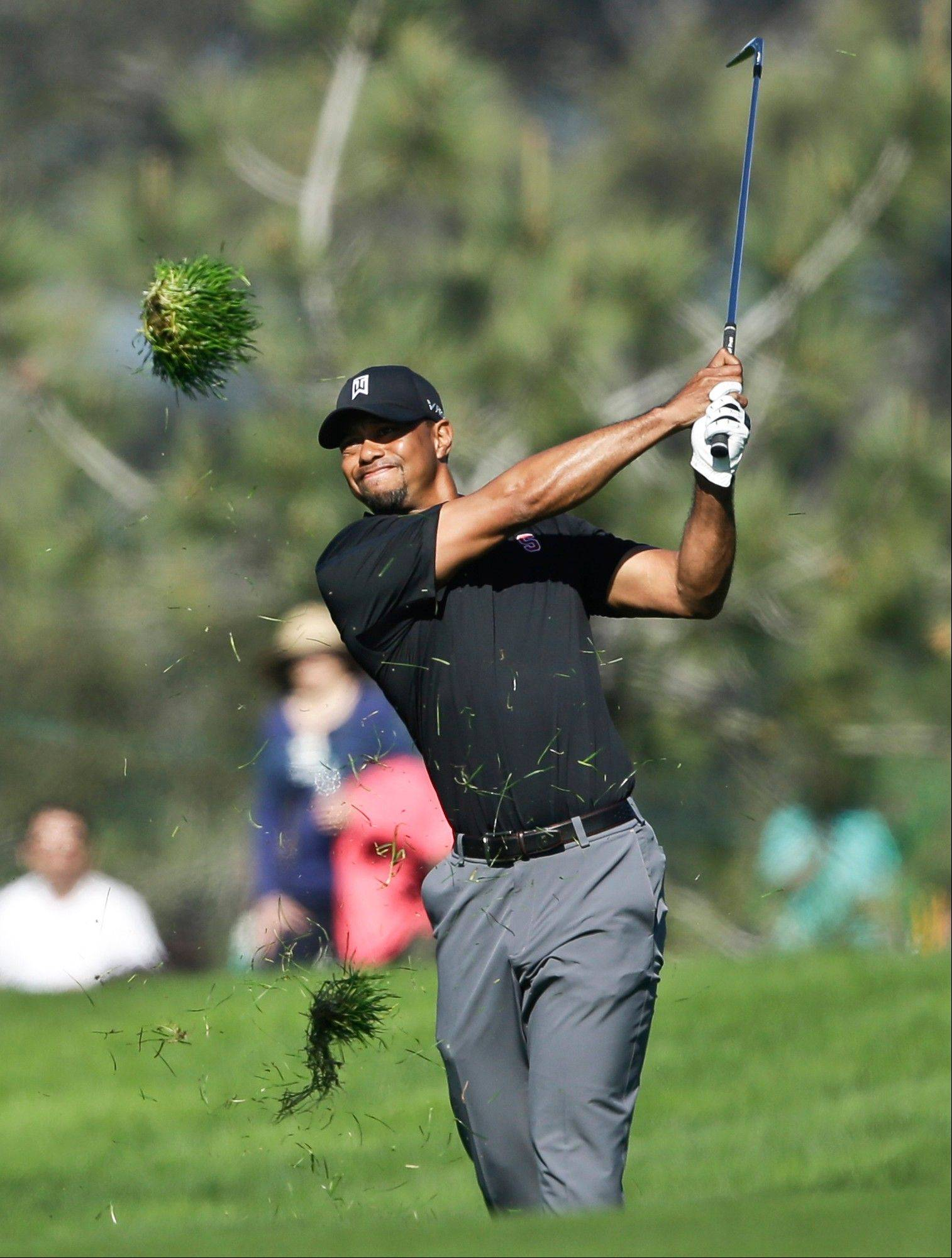 Tiger Woods watches his approach shot on the second hole of the South Course at Torrey Pines during the third round of the Farmers Insurance Open golf tournament Saturday, Jan. 25, 2014, in San Diego. Woods bogeyed the hole.