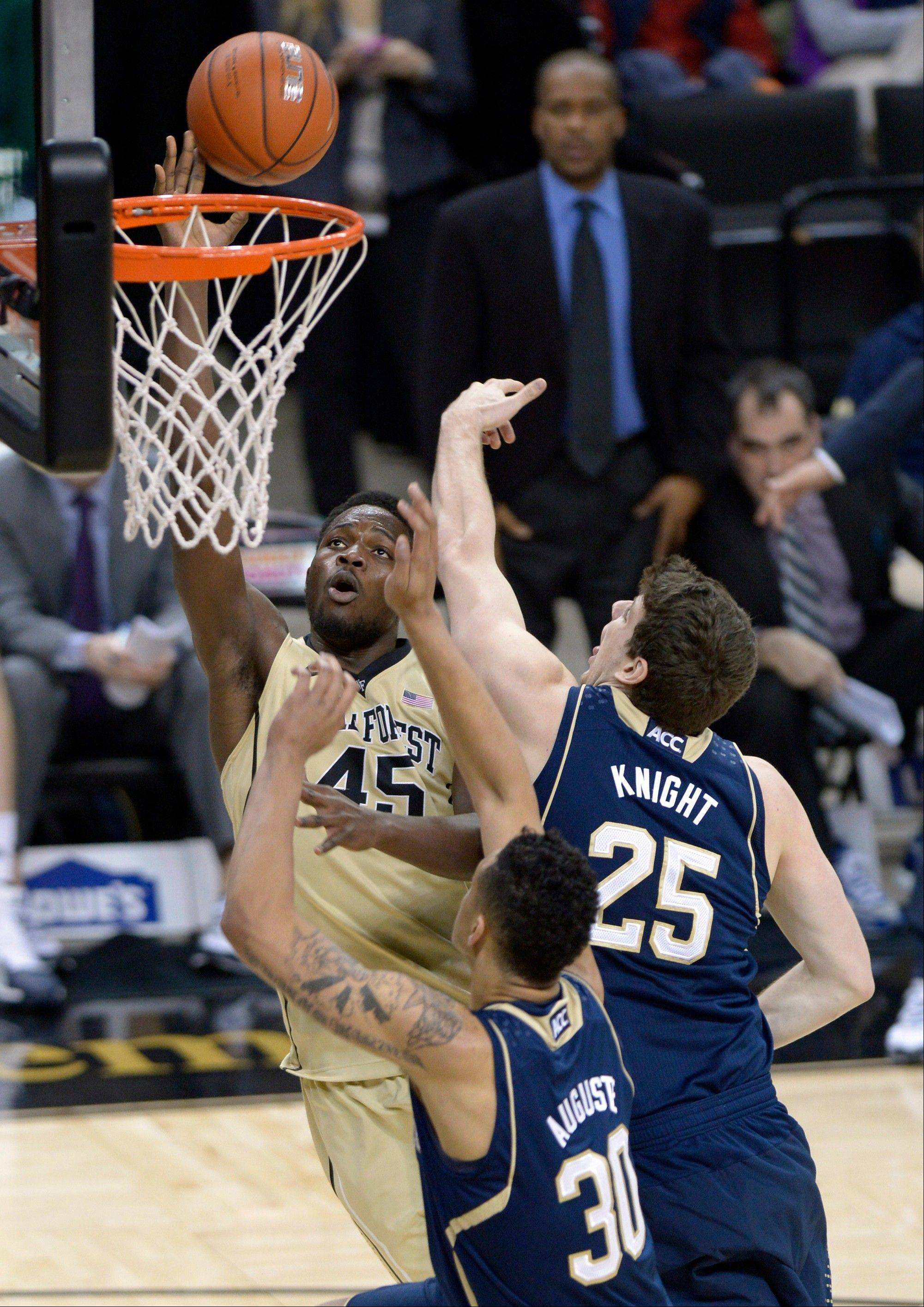 Wake Forest forward Arnaud William Adala Moto (45) gets by the Notre Dame forwards Tom Knight (25) and Zach Auguste (30) during the first half of an NCAA college basketball game at the Joel Coliseum in Winston-Salem, N.C., Saturday, Jan. 25, 2014.