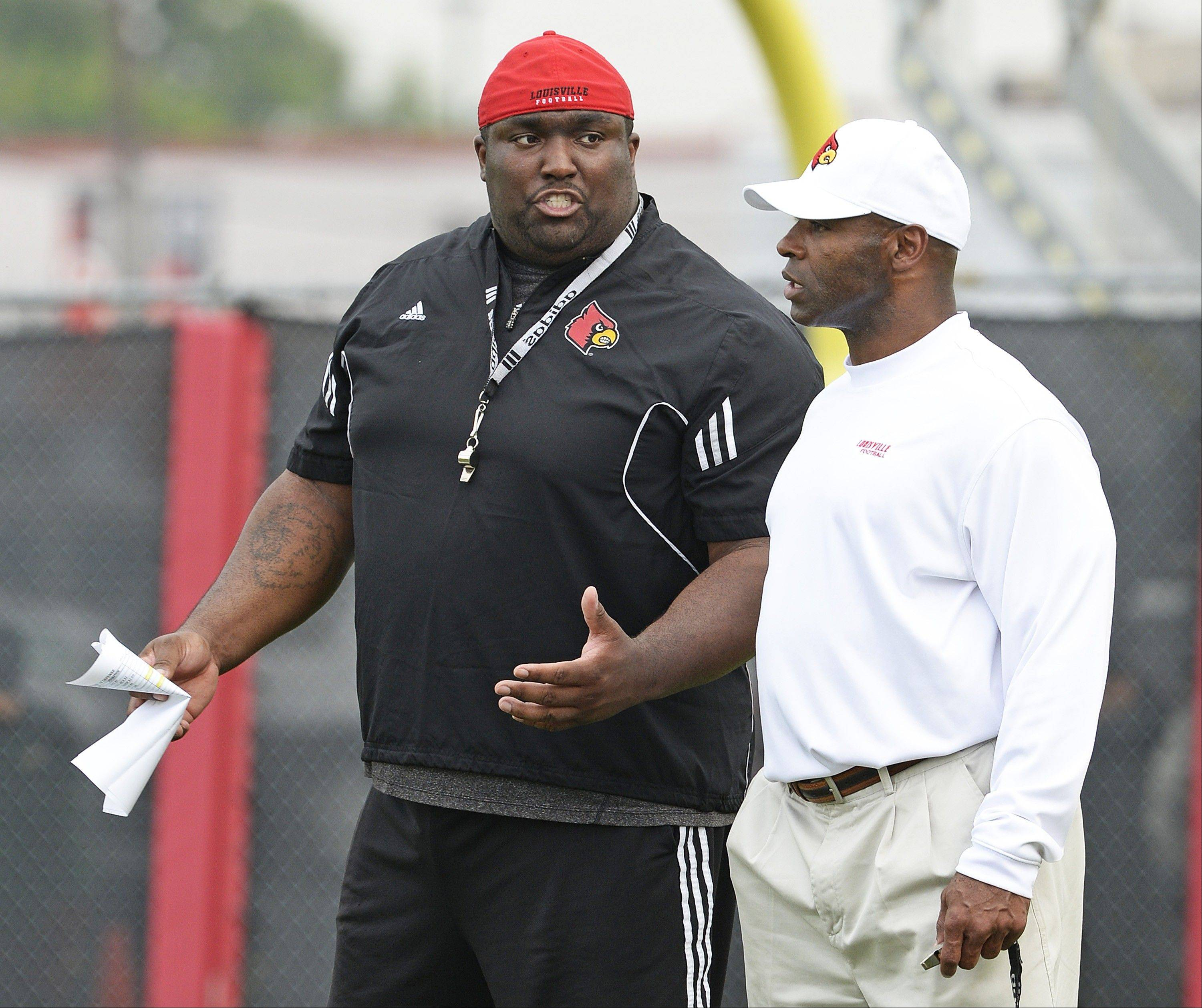 Former Louisville defensive line coach Clint Hurtt, left, helped put together the No. 1 college defense with head coach Charlie Strong last season. Hurtt has joined the Bears as a defensive line assistant.