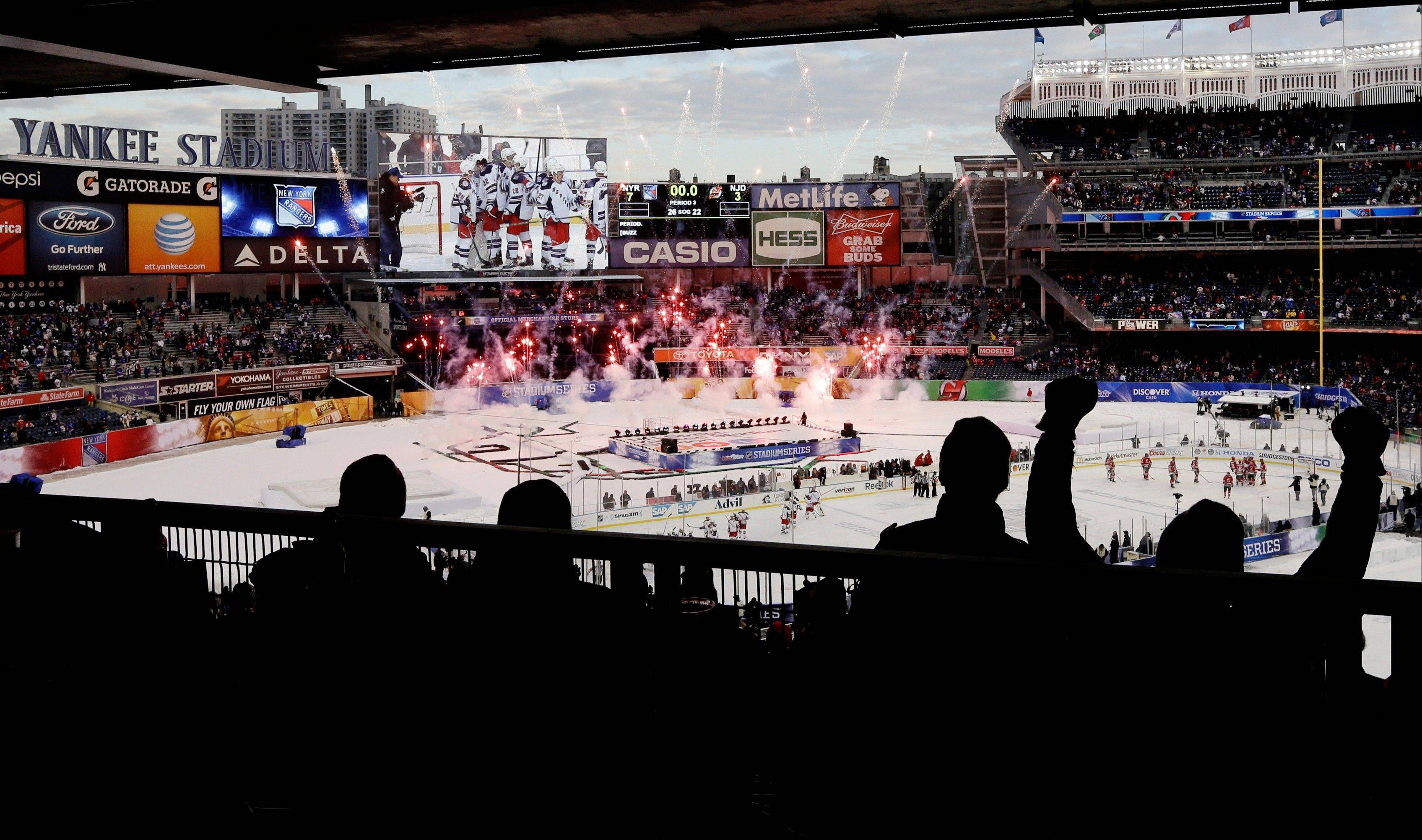 New York Rangers fans cheer during a pyrotechnics display after an outdoor NHL hockey game against the New Jersey Devils Sunday, Jan. 26, 2014, at Yankee Stadium in New York. The Rangers won the game 7-3. (AP Photo/Frank Franklin II)