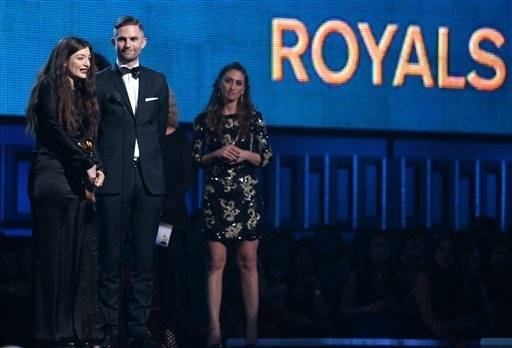 "Lorde, left, and Joel Little accept the award for song of the year for ""Royals,"" as presenter Sara Bareilles looks on at right."