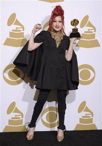 "Cyndi Lauper poses in the press room with the award for best musical theater album for ""Kinky Boots."""