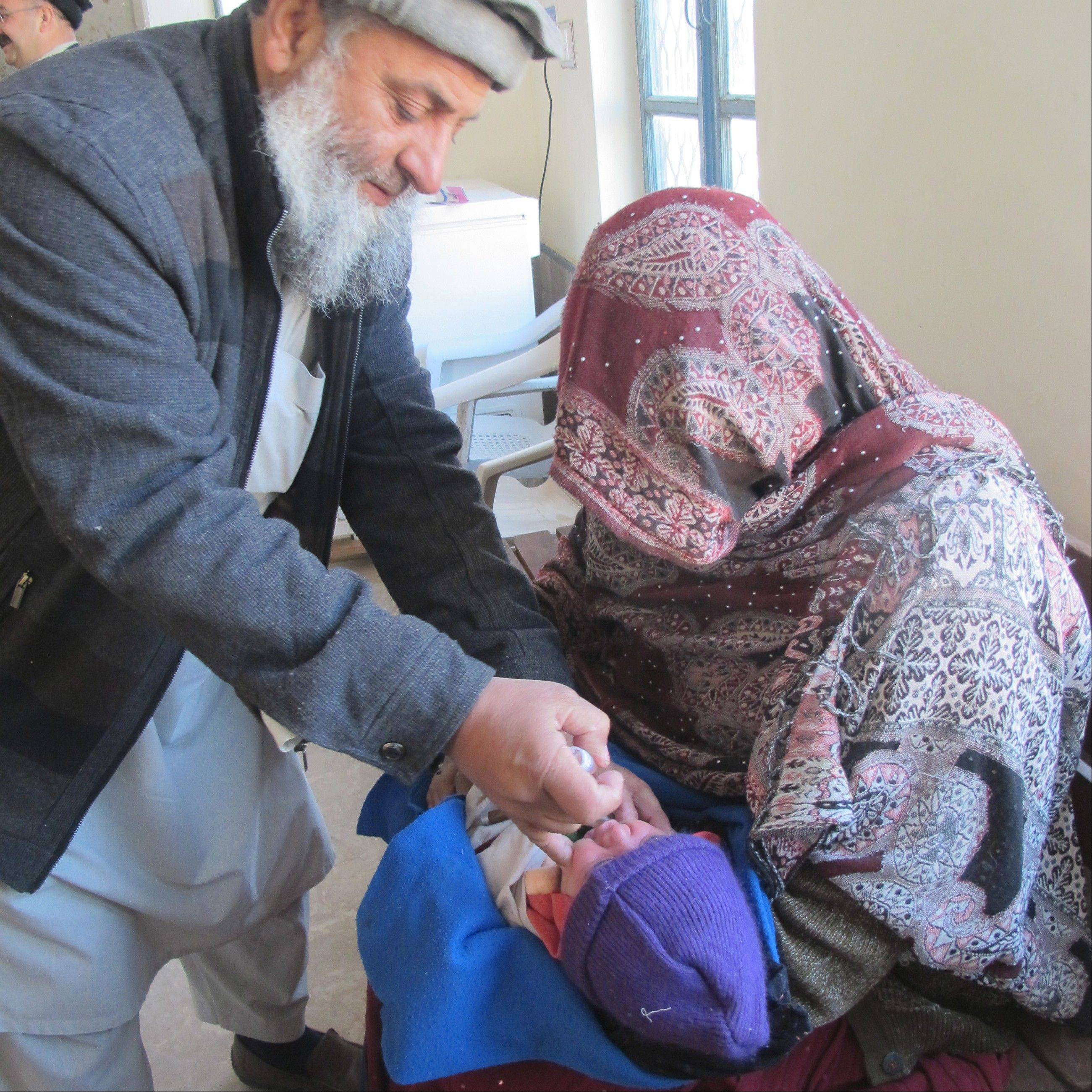 Jamal Shah, left, and an assistant vaccinate a one-month-old infant against polio on Jan. 3, in the Akora Khattak region of northwest Pakistan.