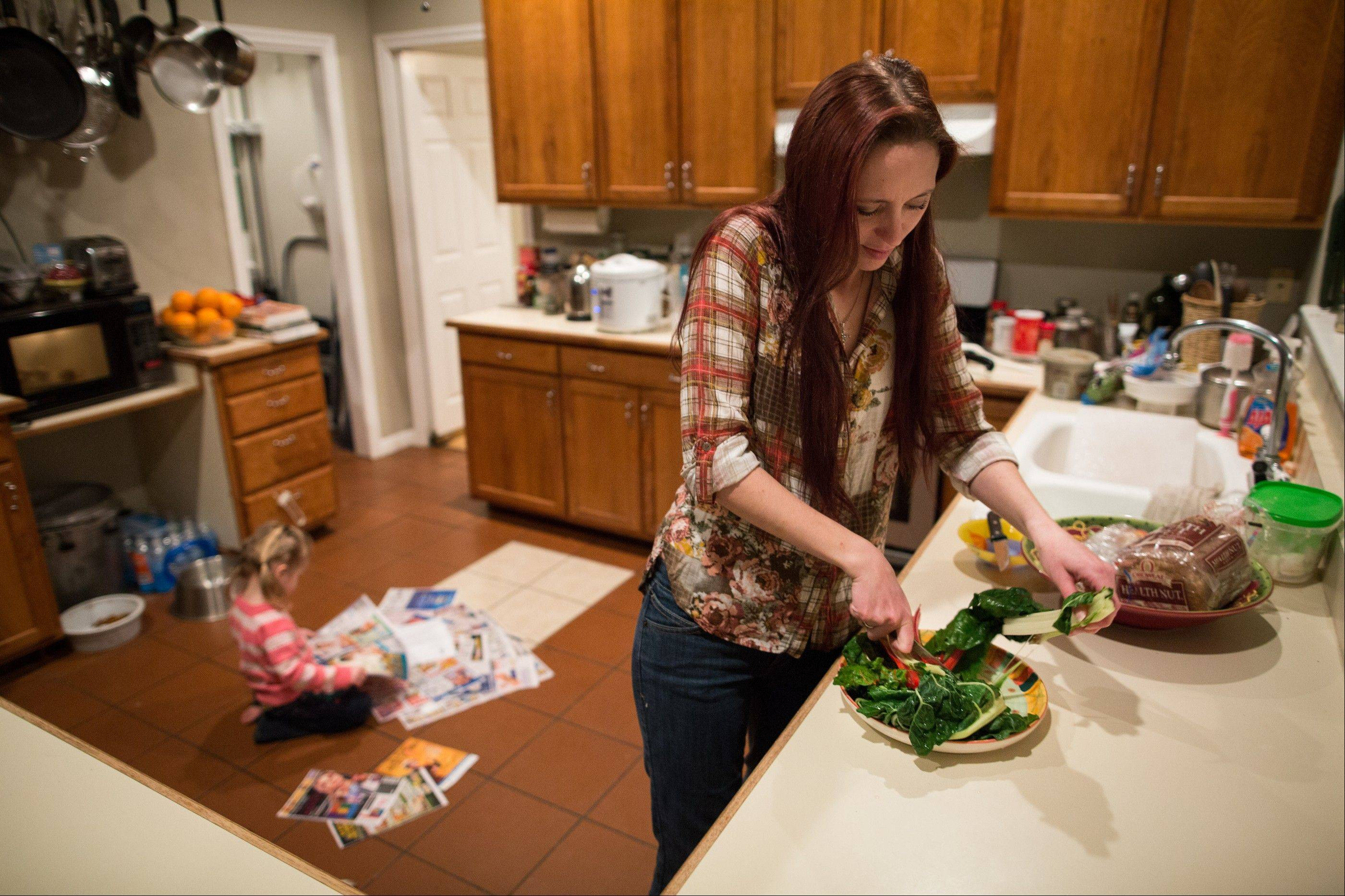Maggie Barcellano prepares dinner at her father's house in Austin, Texas. Barcellano, who lives with her father, enrolled in the food stamps program to help save up for paramedic training while she works as a home health aide and raises her three-year-old daughter.