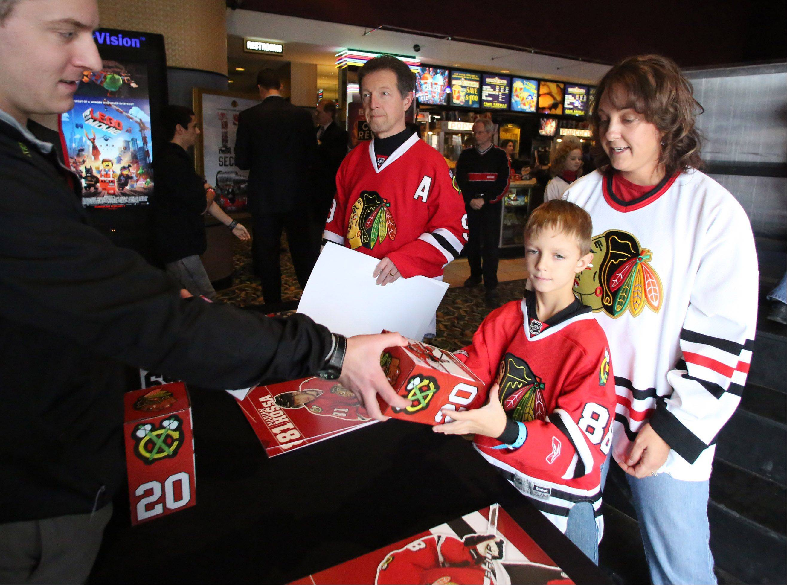 "Cody Rakoncay, 7, of Lake Villa, with his mom, Ann, won a Blackhawks player bobblehead Sunday playing the puck drop game before a screening of the film ""17 Seconds"" at Classic Cinemas Theater in Elk Grove Village. The event, presented by the Daily Herald and the Blackhawks, also featured autograph signings and giveaways."