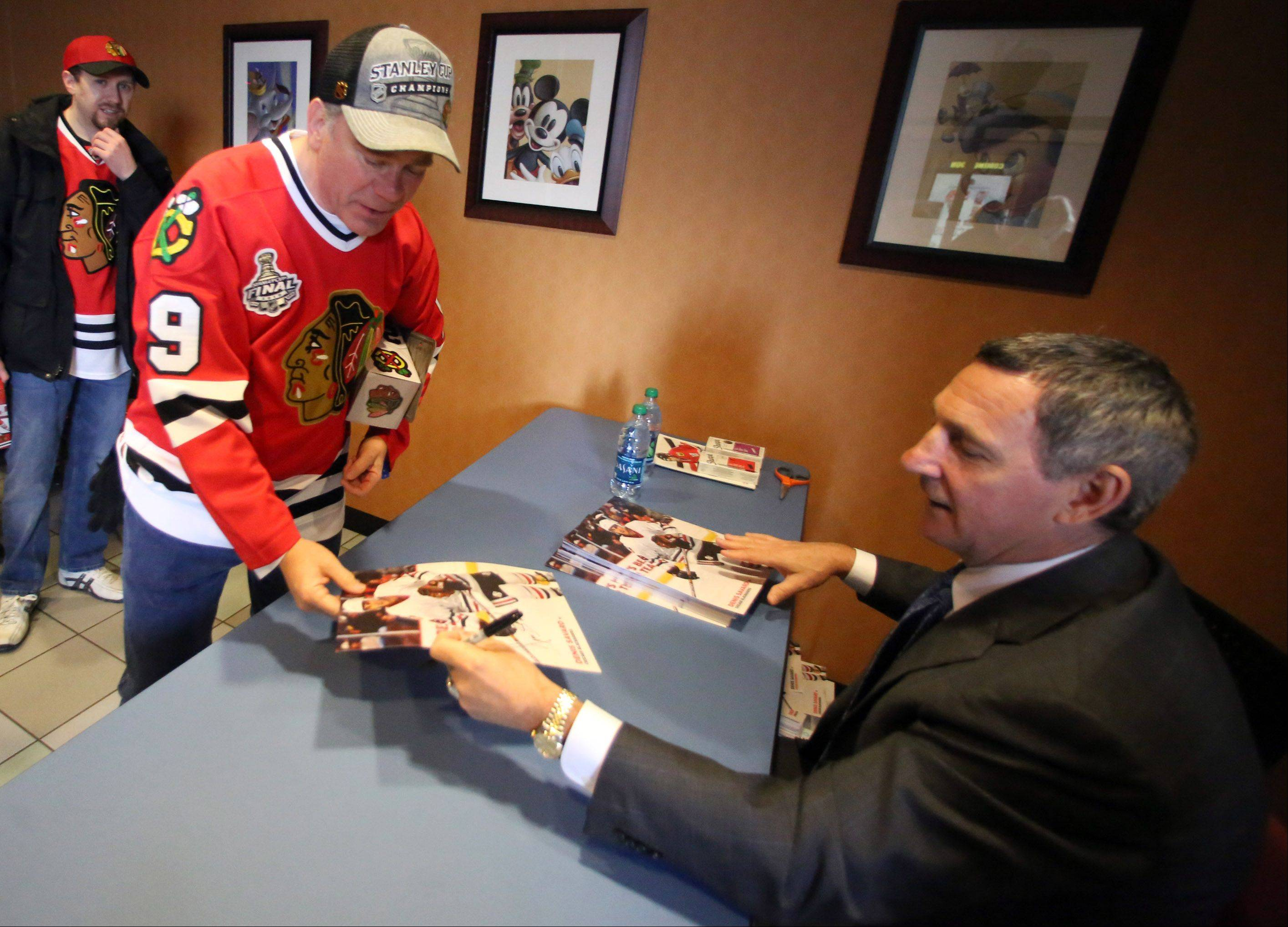 "Former Chicago Blackhawks star Denis Savard signs an autograph for Ken Perez of Itasca after a screening of the film ""17 Seconds"" on Sunday at Classic Cinemas Theater in Elk Grove Village. The event was presented by the Daily Herald and the Blackhawks."