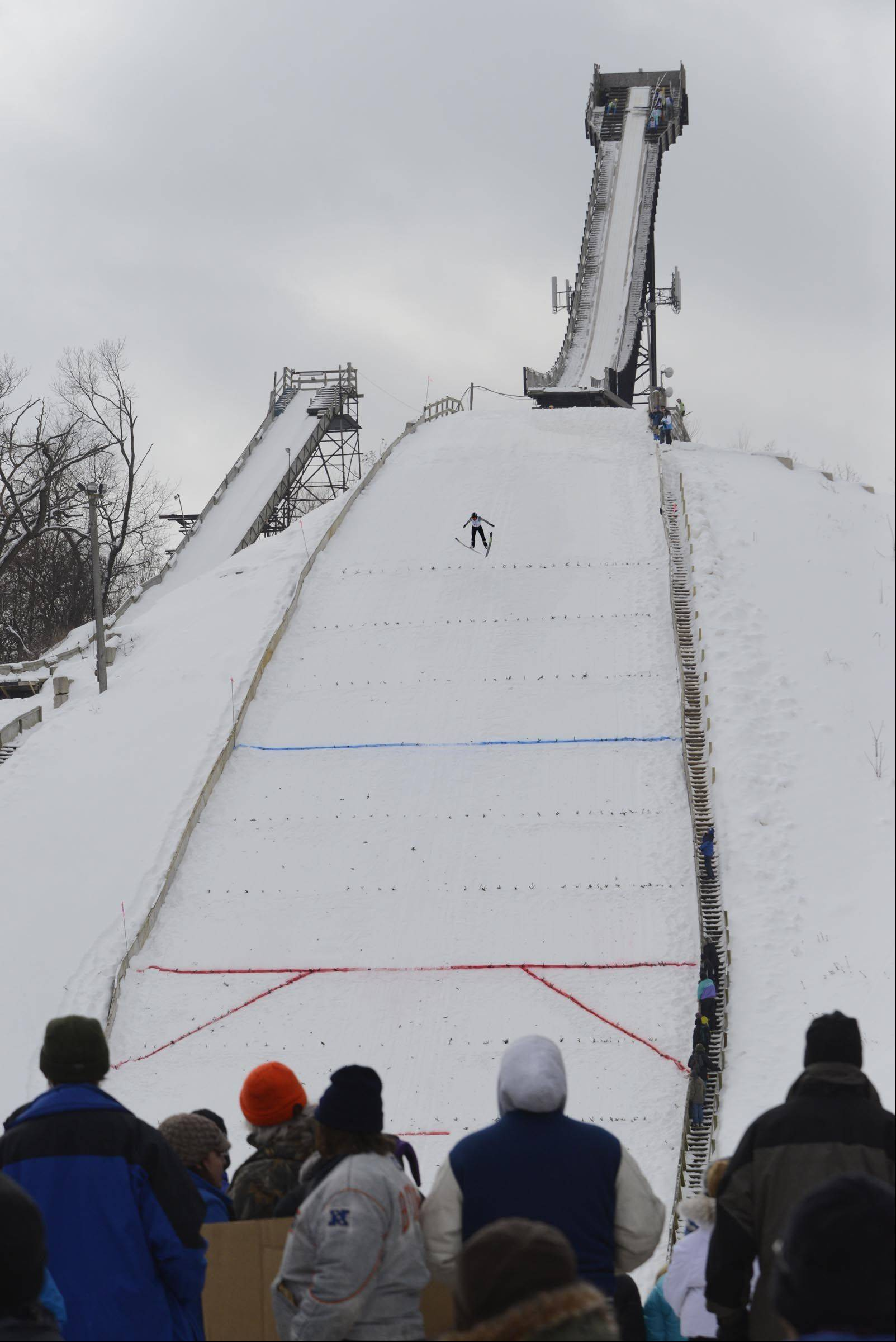 Somer Schrock, 17, of Minnesota, comes down the 70-meter hill Sunday at the Norge International Ski Jumping Tournament in Fox River Grove. More than 60 skiers competed in Sunday's event.