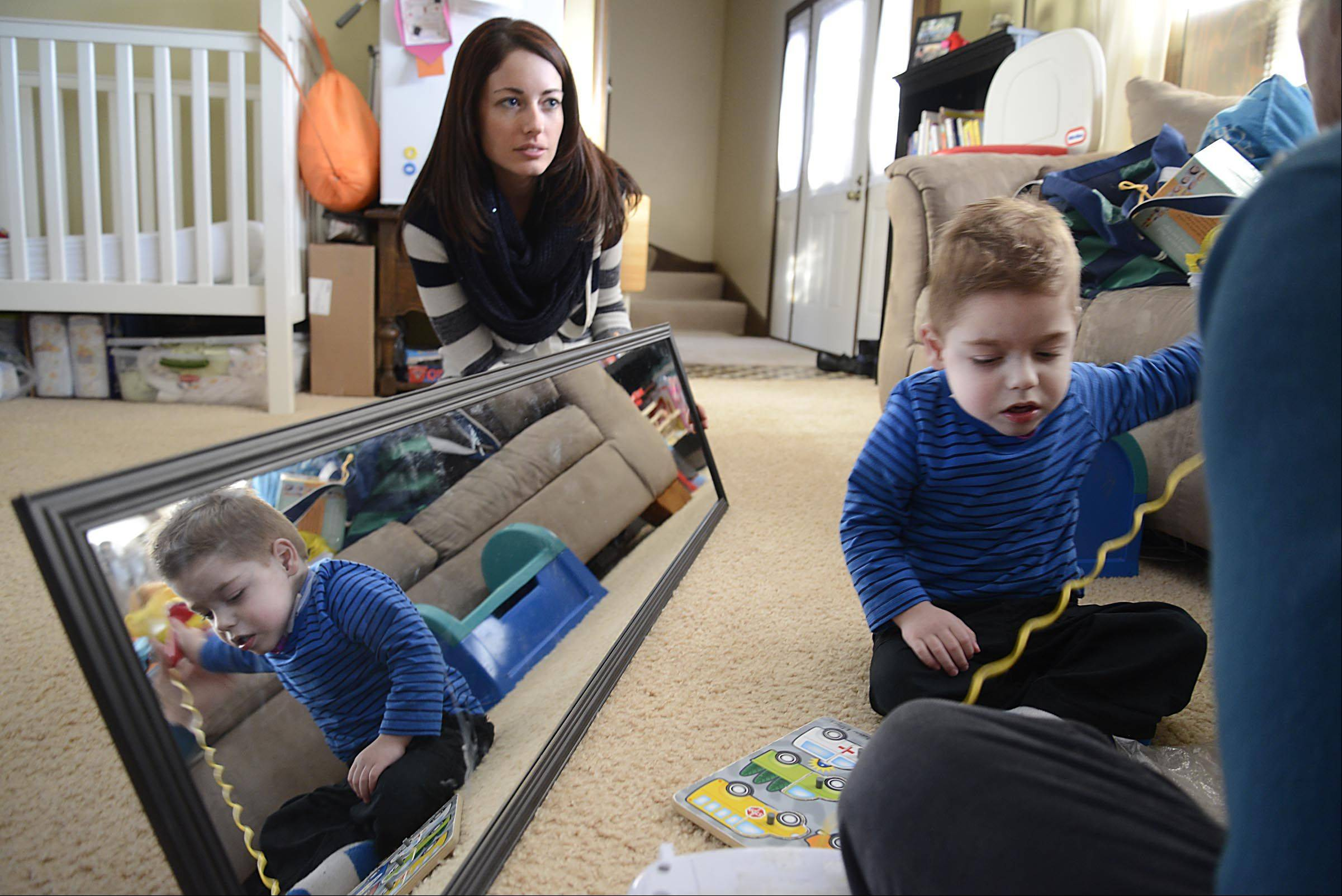 Jennifer Rigler holds a mirror and watches as her son Andrew works with therapist Mary Kochanski in their Bartlett home. The two-year-old was born prematurely and has therapy to promote his development.
