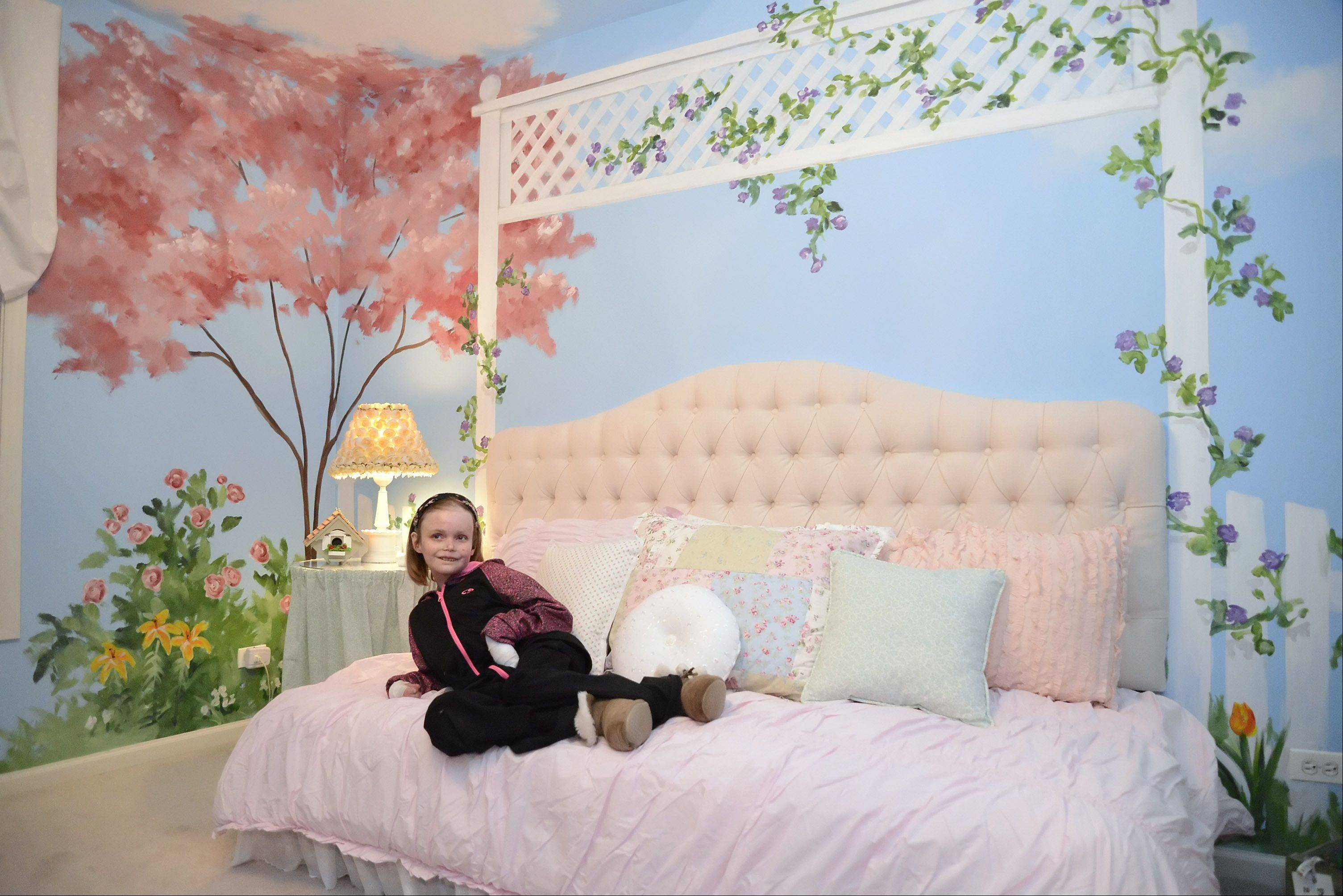Catharine Steiner, 16, of St. Charles, settles onto her bed in her made-over bedroom for the first time on Thursday. Special Spaces Chicagoland, a non-profit organization, creates dream bedrooms for children with life-threatening medical conditions. Catharine was born with Recessive Dystrophic Epidermolysis Bullosa, a rare genetic connective tissue disorder. She requested a garden theme with blues, pinks, greens and purples.