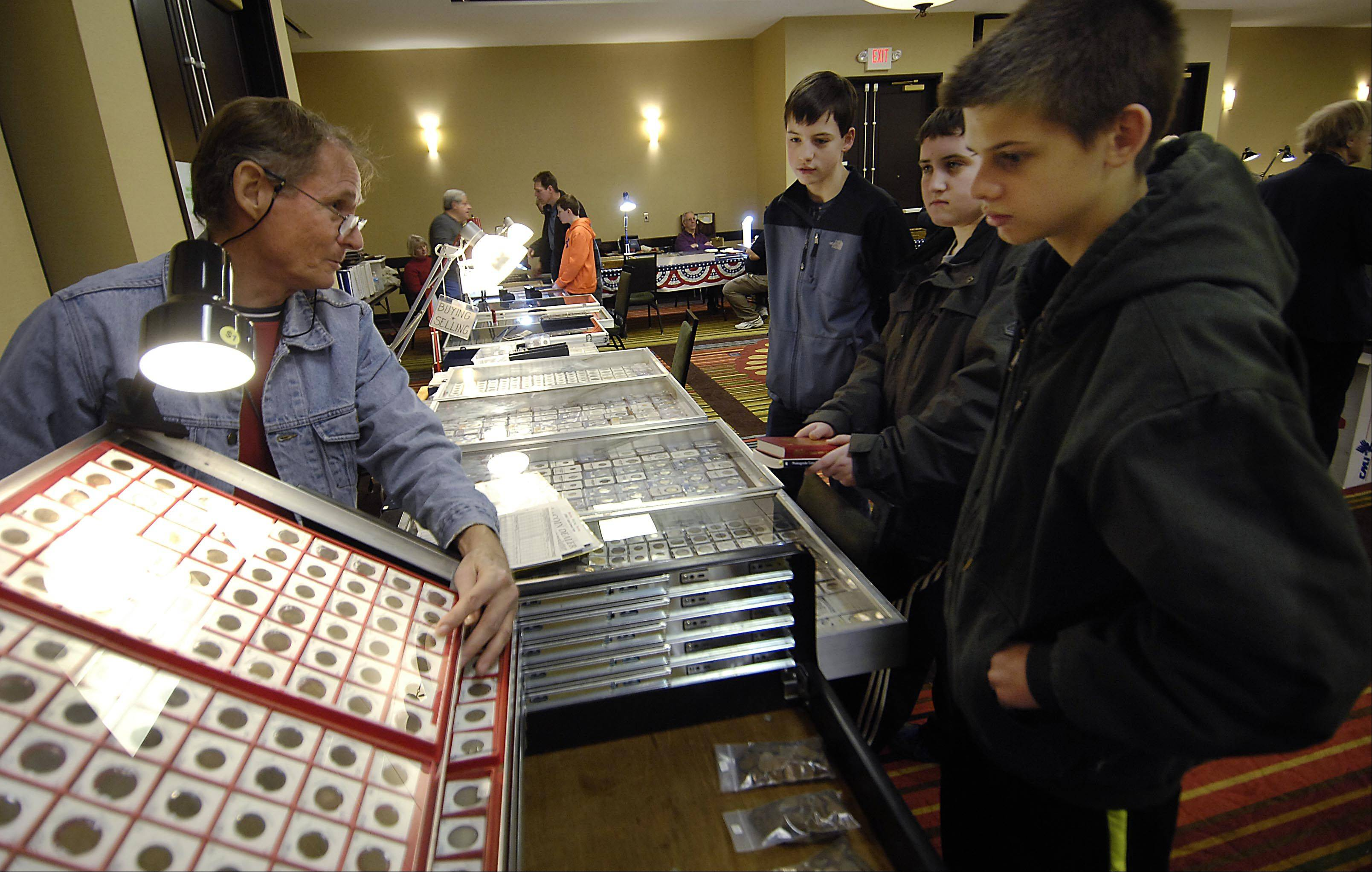 Coin dealer Fred Dennis, of Geneva, talks with 13-year-olds Connor Bystrom, Alex Kelly and Marshall Bott, friends from Lake Zurich, Sunday at the Geneva Coin Club's Mid-Winter Classic Coin Show at the Holiday Inn on Airport Road in Elgin. Dennis is the club chairman.
