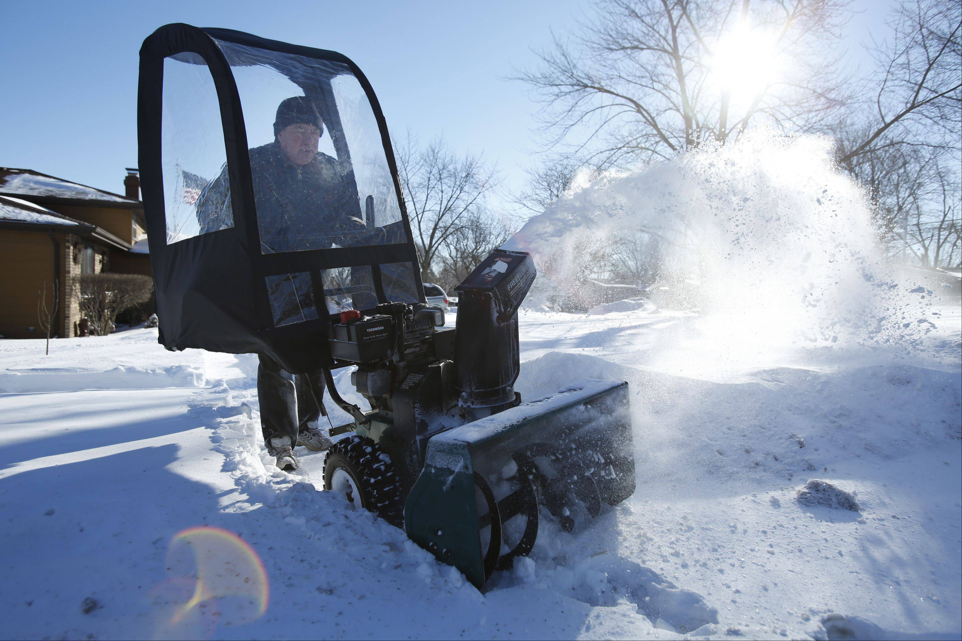 "Andy Patete, of South Elgin, blasts the new snow from the sidewalks Tuesday morning near his Spring Street home, behind the protection of a plastic shield affixed to his snow thrower. Patete said the shield does keep things a bit warmer for him while he works. ""At least it keeps the snow from blowing in your face,"" he said."