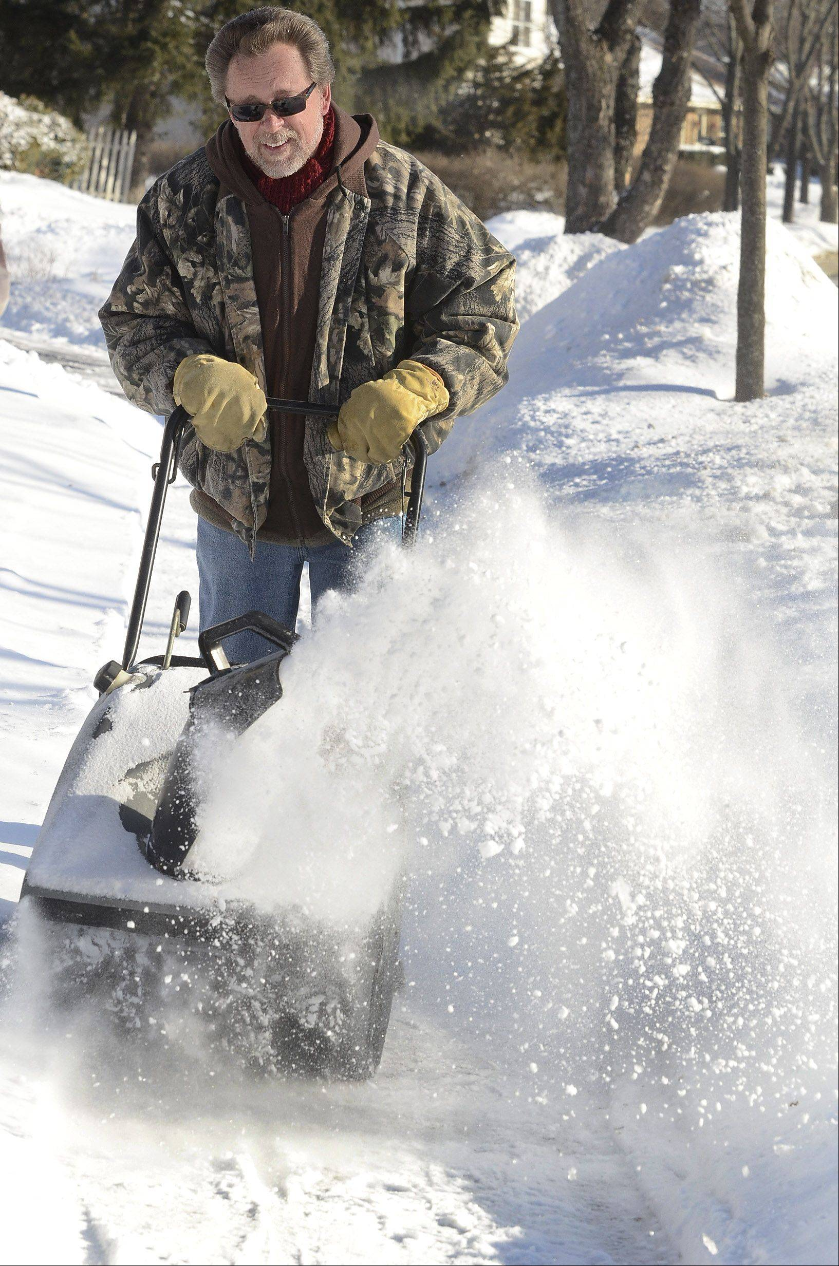 Ray Fossum, of Hanover Park, clears a path in front of his home on Yorkshire Drive. He says he's been keeping up with it this winter because he's now retired and has the time.
