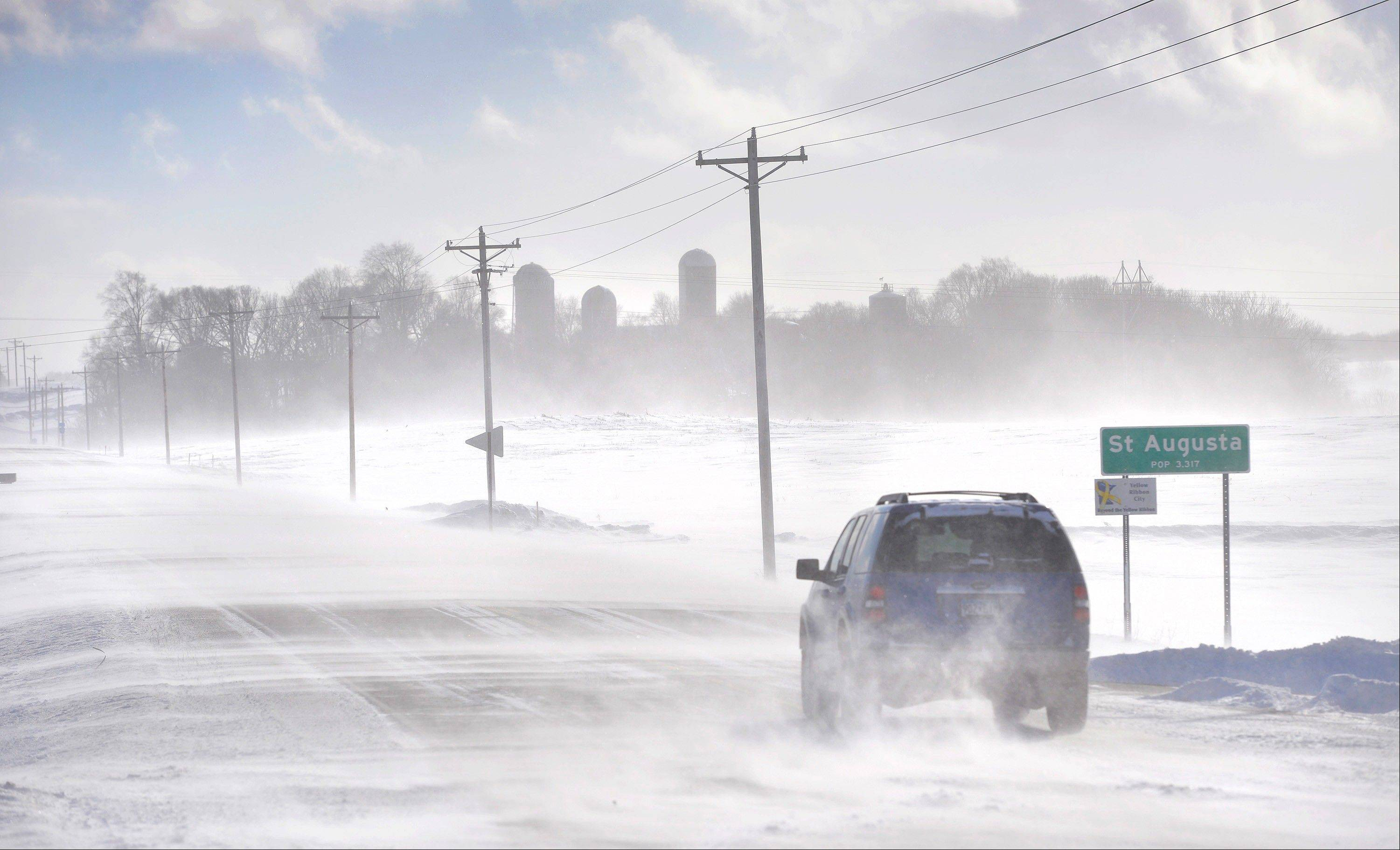 An SUV ventures past the St. Augusta, Minn., city limits sign in near white-out conditions Sunday afternoon. An unusual weather pattern driving bitterly cold air from the Arctic Circle south across a huge swath of the Midwest is expected to send temperatures plummeting Monday from Minneapolis to Louisville, Ky., the latest punch from a winter that is in some areas shaping up as one of the coldest on record.