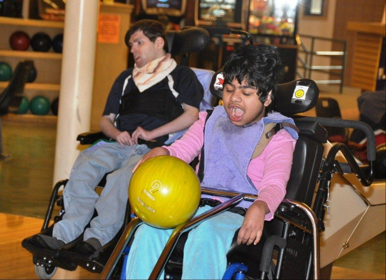 A resident of Little Angels Center for Exceptional Care in Elgin, Sobia uses special equipment to bowl during last year's SUPERBowling party and fundraiser at Arlington Lanes in Arlington Heights. Sponsored by the Schaumburg-Hoffman Lions Club, the event, which starts at 4 p.m. on Super Bowl Sunday, features bowling, food, an auction and TVs showing the game.