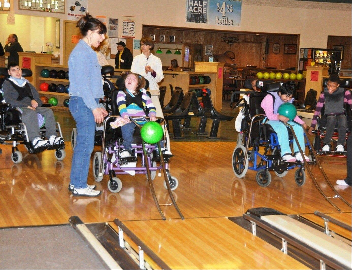 Using special equipment, residents of Little Angels Center for Exceptional Care in Elgin bowl during last year's SUPERBowling party and fundraiser at Arlington Lanes in Arlington Heights. Sponsored by the Schaumburg-Hoffman Lions Club, this year's event, which starts at 4 p.m. on Super Bowl Sunday, features bowling, food, an auction and TVs showing the game.
