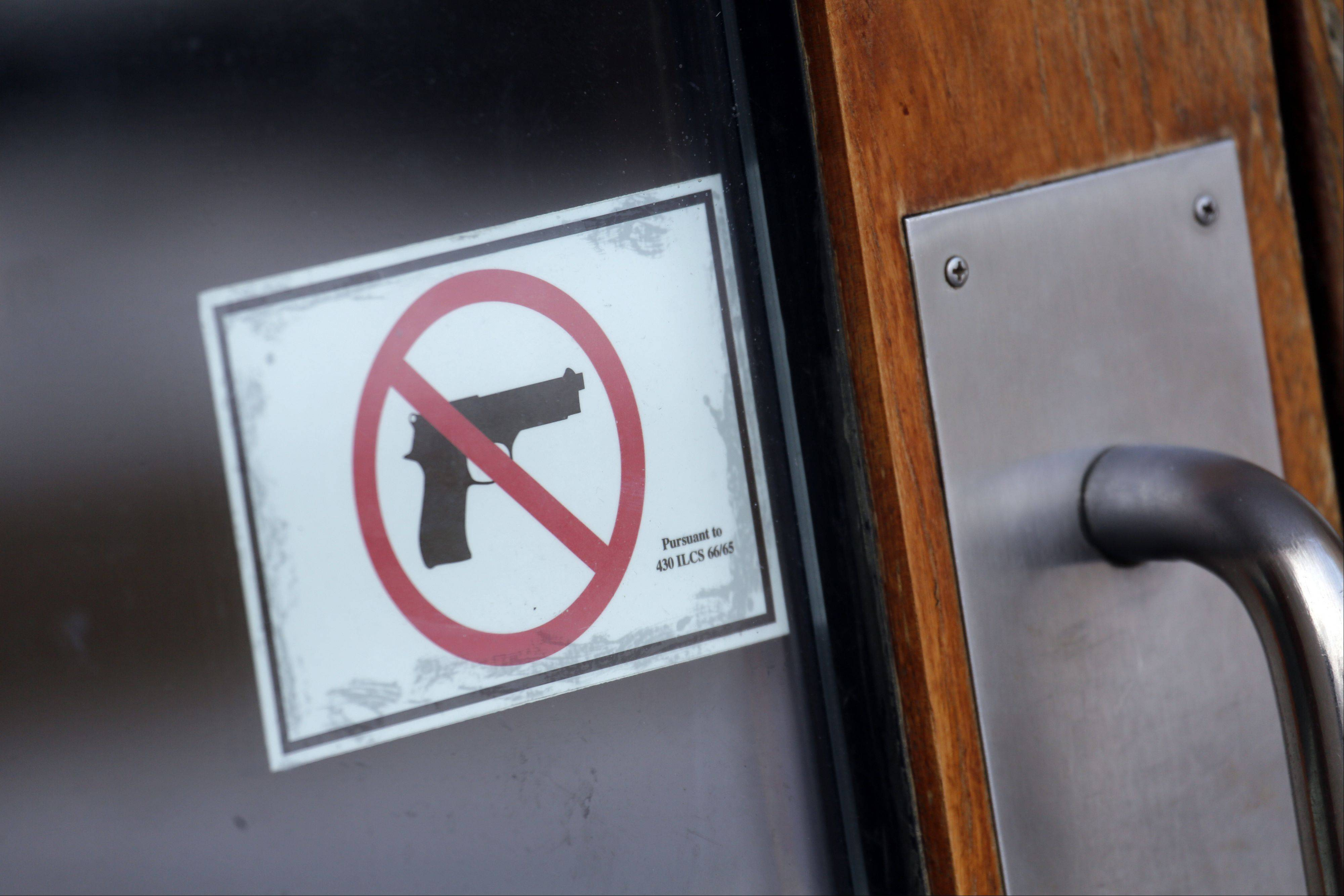Gun-free zone signs are plastered at the Kane County Judicial Center. The state's new concealed carry law prohibits anyone other than law enforcement officials from carrying concealed handguns into public buildings.