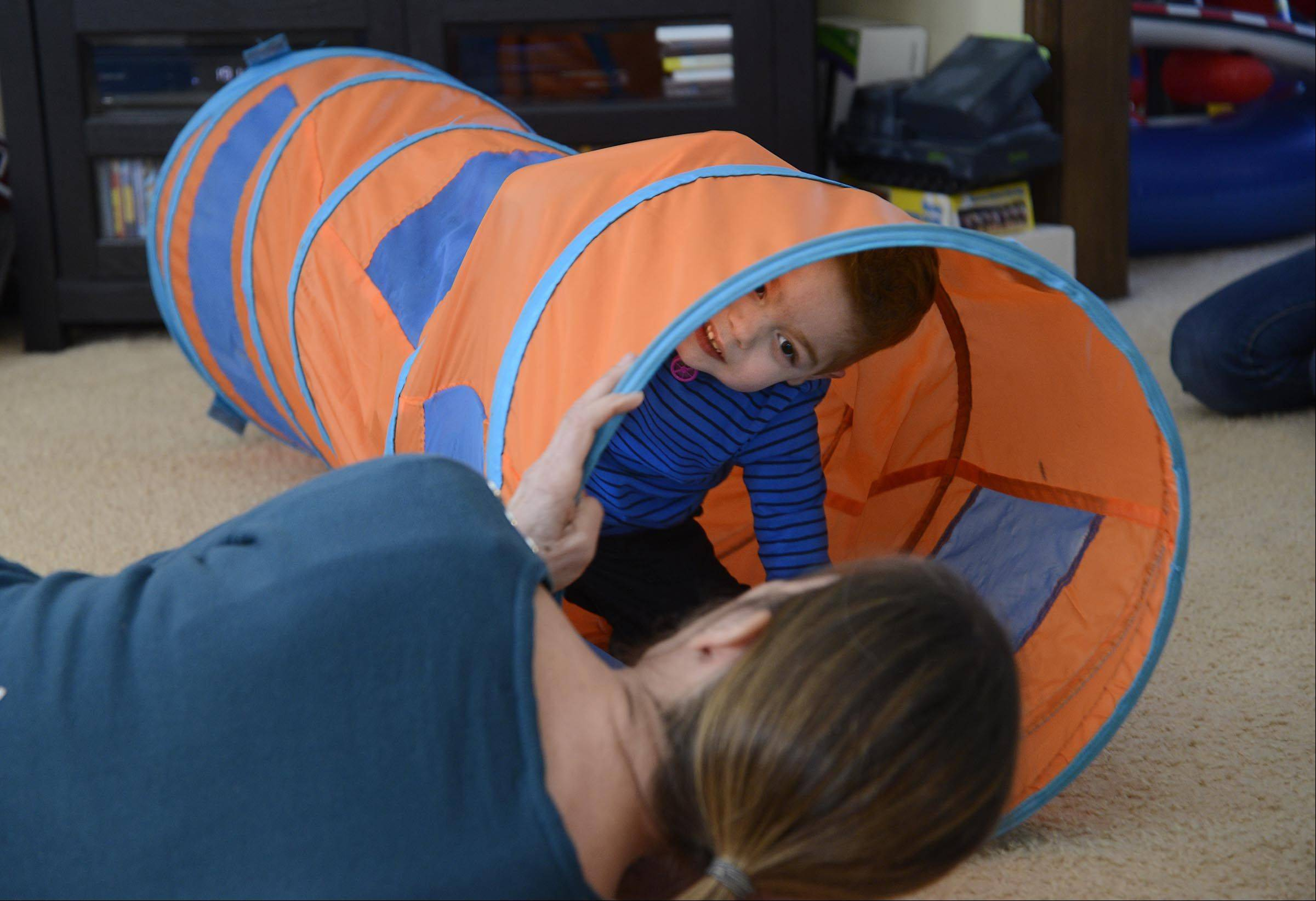 "Andrew Rigler crawls through a tunnel. ""He's always laughing,"" his mom Jennifer Rigler said. ""I think he's loving life."""