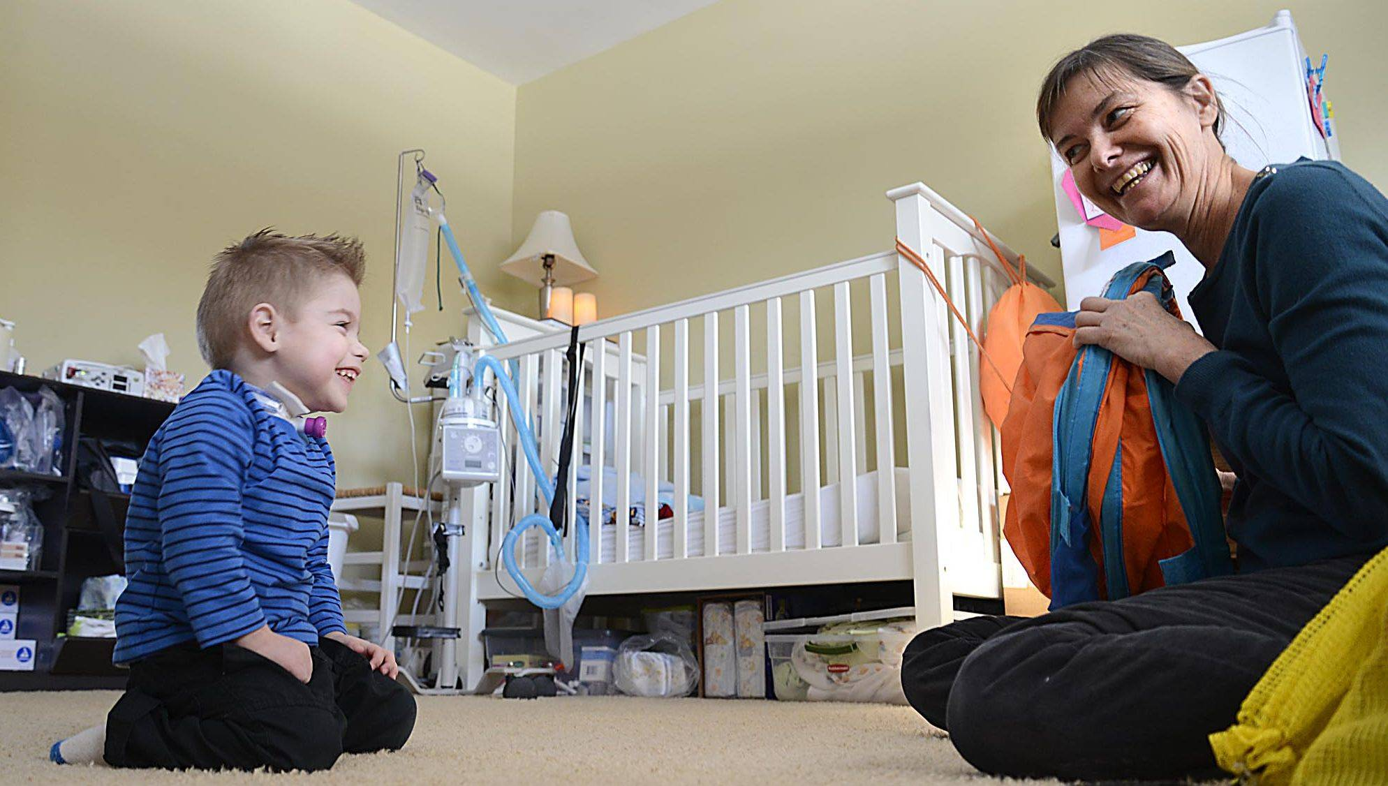 Andrew Rigler laughs when he spots the tunnel he uses for developmental therapy in his Bartlett home.