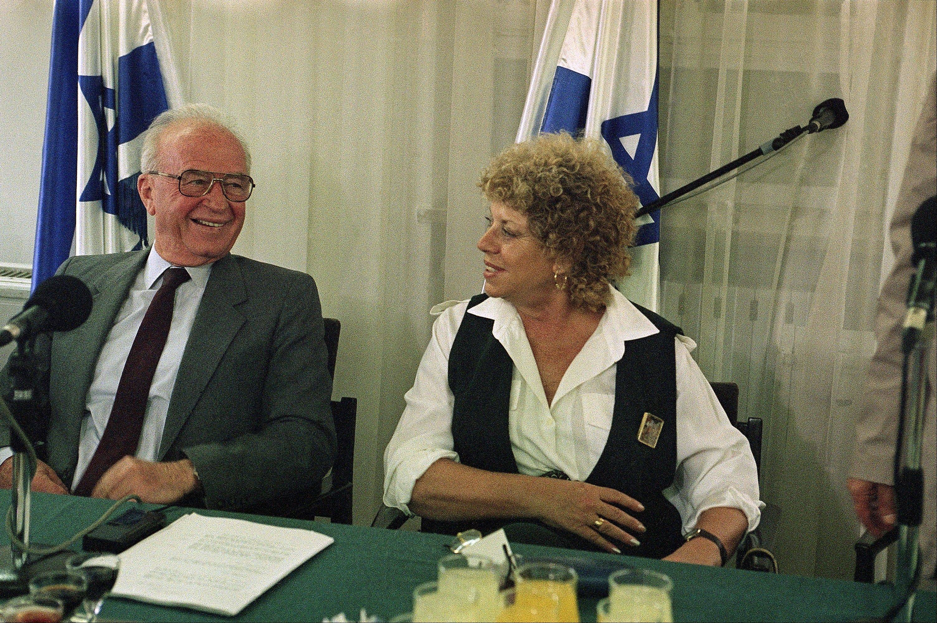Israeli Prime Minister Yitzhak Rabin and Education Minister Shulamit Aloni share a laugh during the signing of a teacher's union contract at the Prime Minister's office in Jerusalem in 1963.