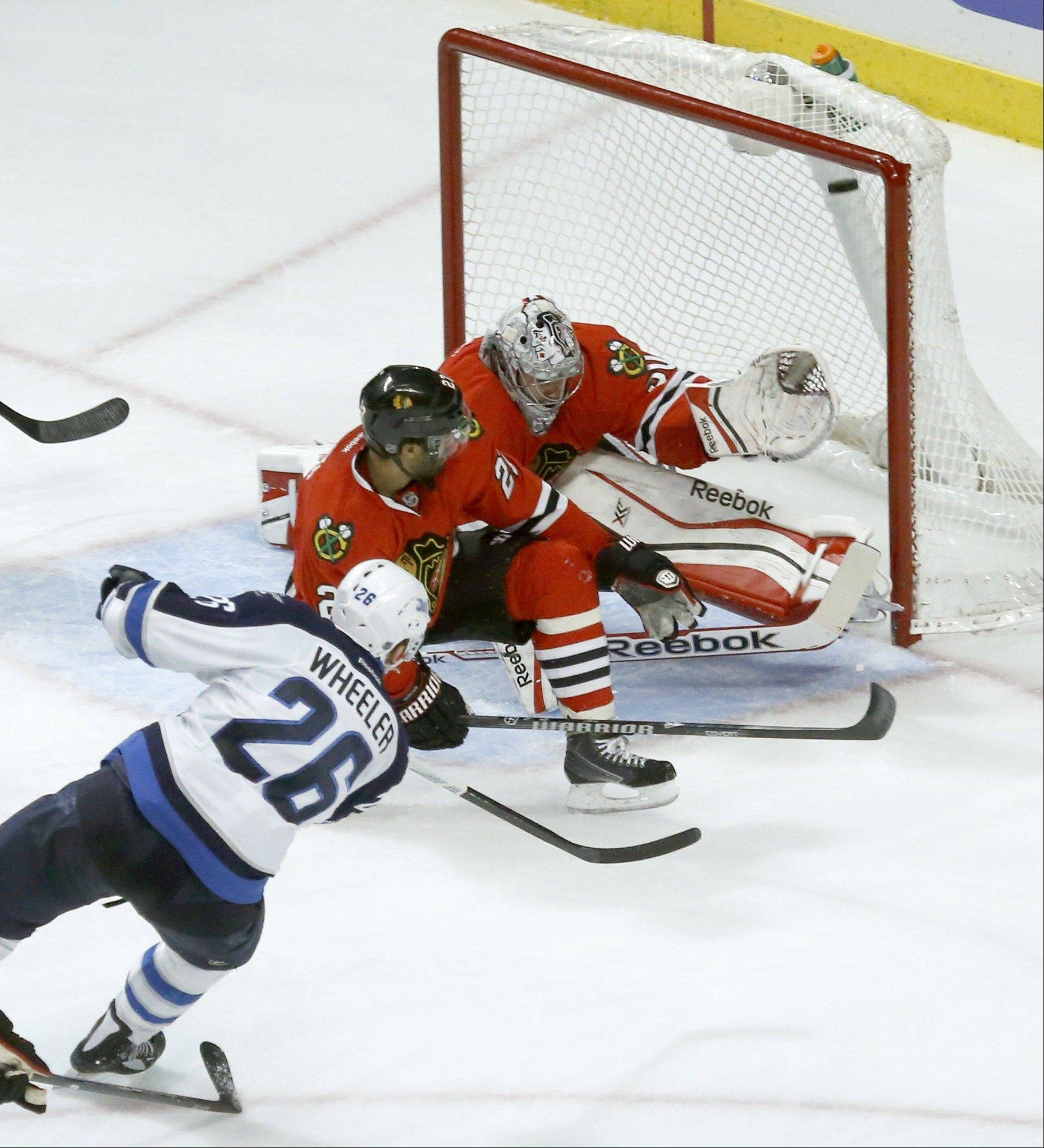 The Jets' Blake Wheeler shoots and scores past Blackhawks defenseman Johnny Oduya and goalie Corey Crawford during Winnipeg's 3-goal third period Sunday night.