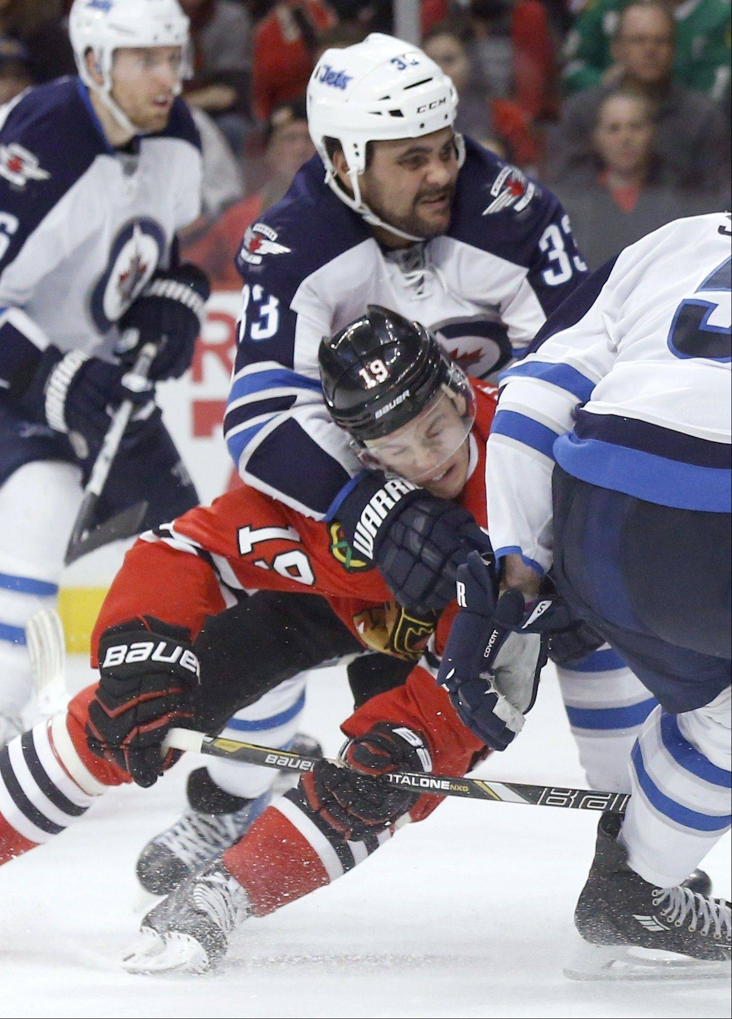 Winnipeg Jets defenseman Dustin Byfuglien (33) takes Chicago Blackhawks center Jonathan Toews (19) down after Toews' shot on goal during the second period of an NHL hockey game Sunday, Jan. 26, 2014, in Chicago.