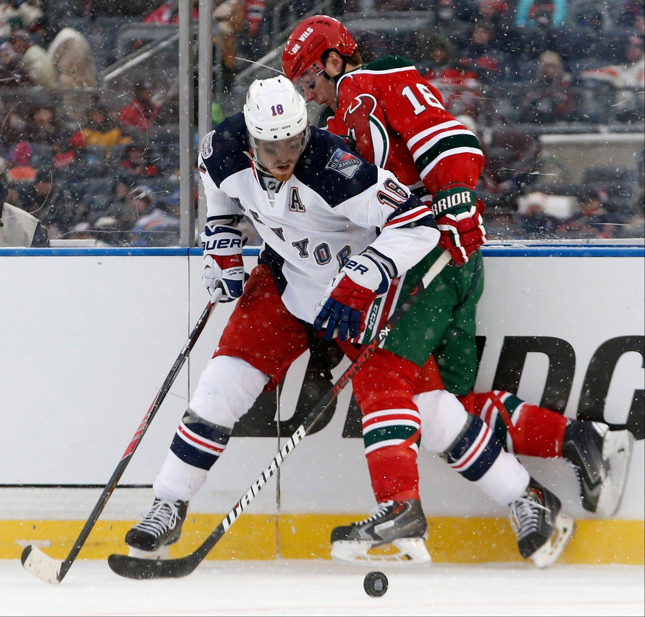 New York Rangers defenseman Marc Staal (18) checks New Jersey Devils right wing Steve Bernier (18) in the second period of a snowy NHL outdoor hockey game at Yankee Stadium in New York, Sunday, Jan. 26, 2014. It is the first time a hockey game has been played in Yankee Stadium.