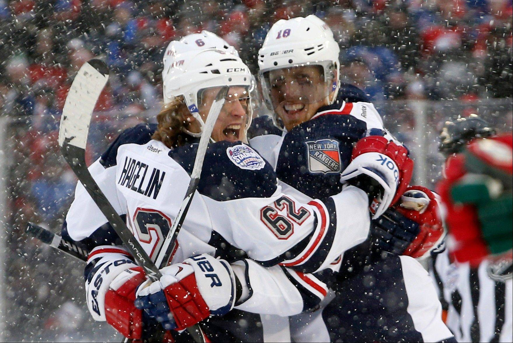 New York Rangers left wing Carl Hagelin (62) celebrates with Rangers defenseman Marc Staal (18) after scoring a goal in the second period of an NHL outdoor hockey game in the snow with New Jersey Devils at Yankee Stadium in New York, Sunday, Jan. 26, 2014. It is the first time a hockey game has been played in Yankee Stadium.
