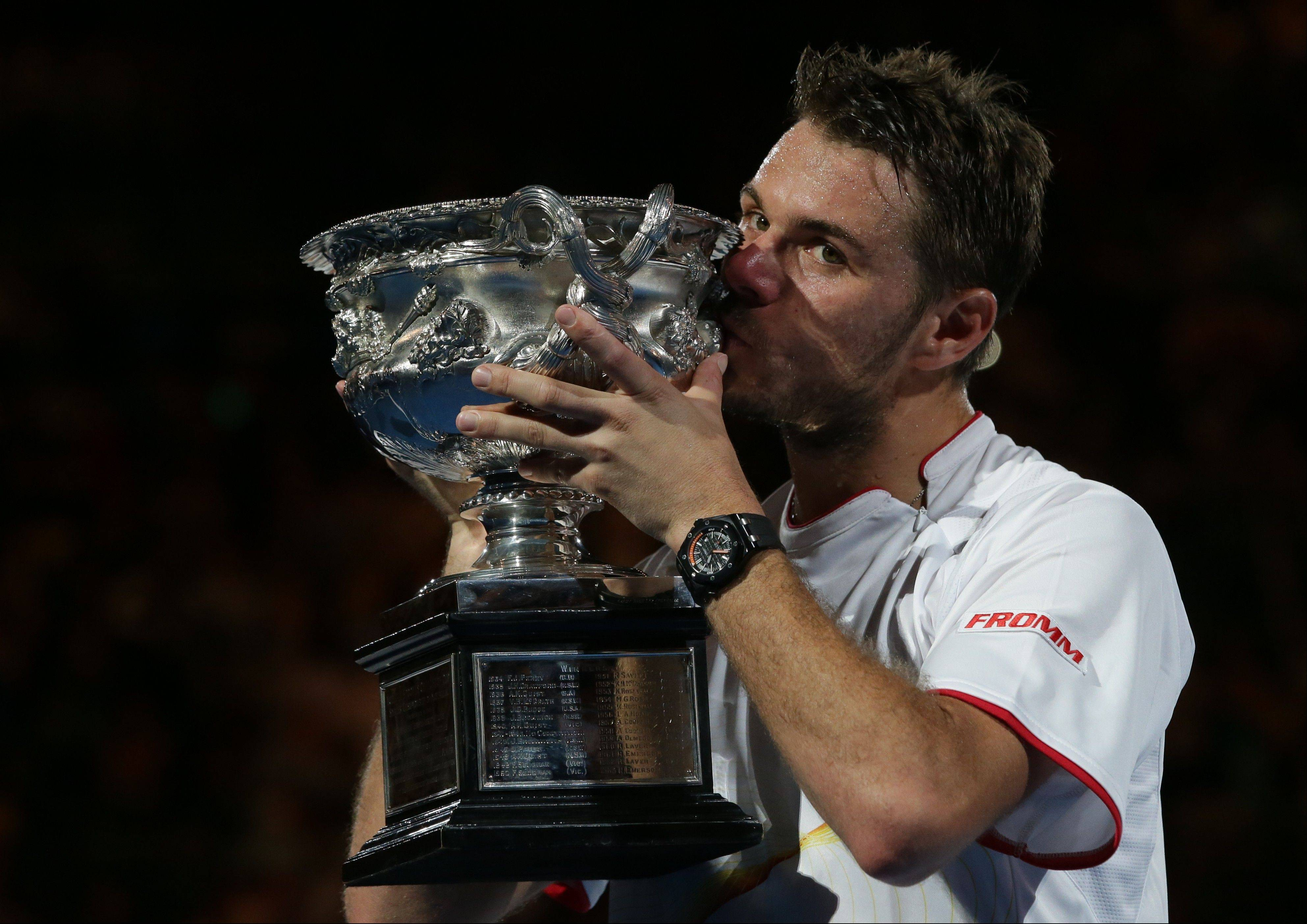 Stanislas Wawrinka of Switzerland kisses the trophy after defeating Rafael Nadal of Spain in the men's singles final at the Australian Open tennis championship in Melbourne, Australia, Sunday.