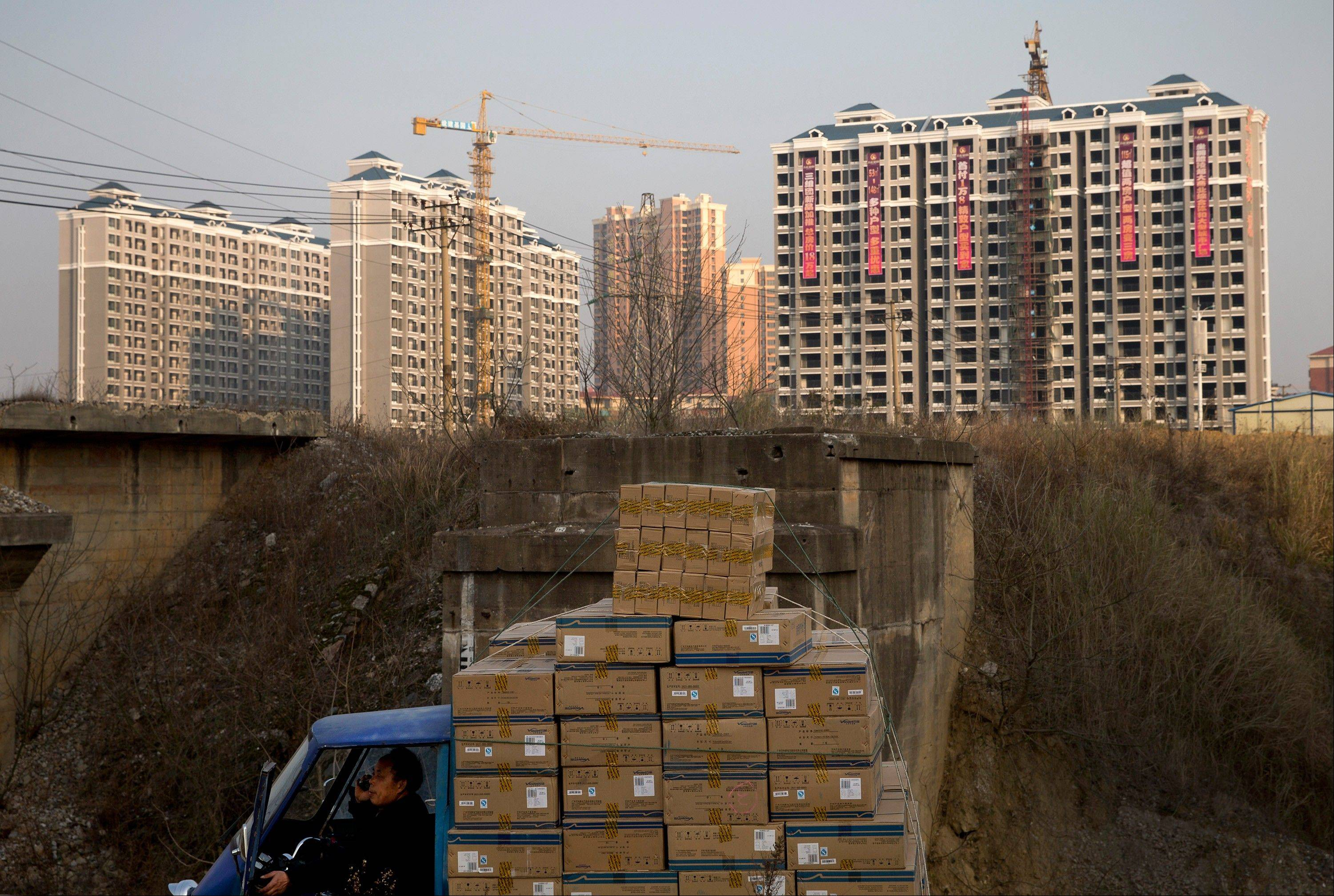 A man talks on a mobile phone inside his tricycle cart loaded with goods near under-construction residential buildings in Changsha, in China�s Hunan province. U.S. investors are being hit with new worries from overseas just as the economy at home appears to be strengthening.