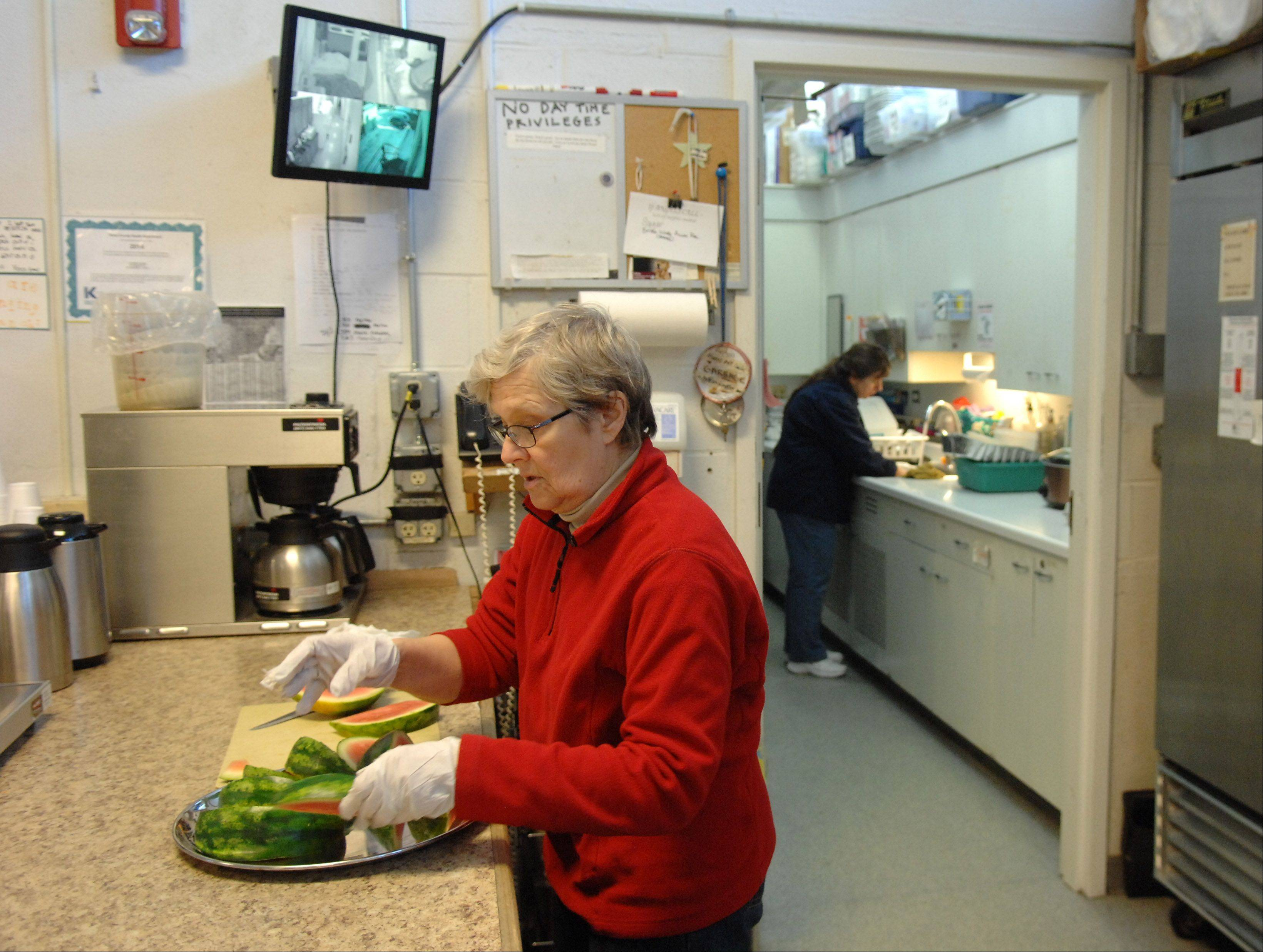 Lazarus House volunteer Nona Koivula of St. Charles cuts watermelon Monday in preparation for lunch. �I�m trying to make it seem a little more like summer,� she said. She�s been volunteering three days a week at the shelter for almost two years. �I�m too old for the Army, so this is how I serve my community and my country.�