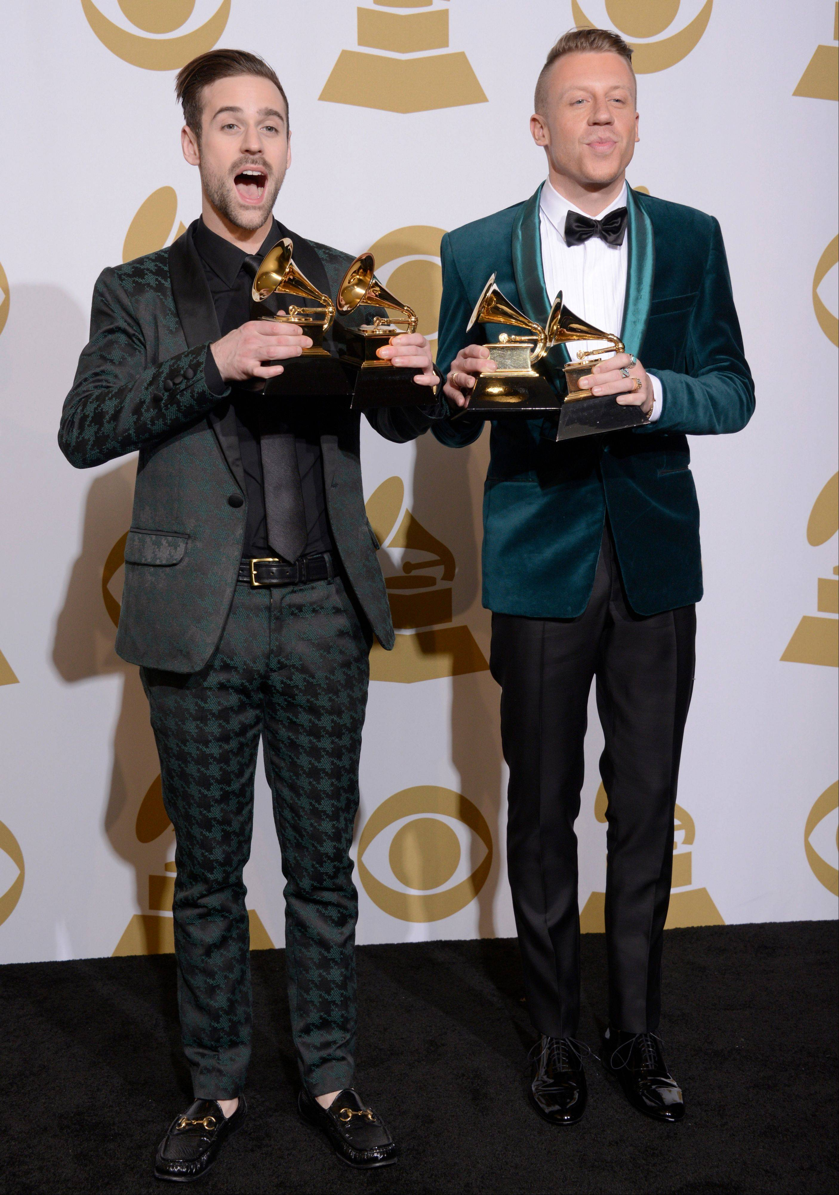 "Ryan Lewis, left, and Macklemore pose in the press room with their awards for best rap performance and best rap song, for ""Thrift Shop,"" best rap album for ""The Heist"" and best new artist at the 56th annual Grammy Awards at Staples Center on Sunday in Los Angeles."