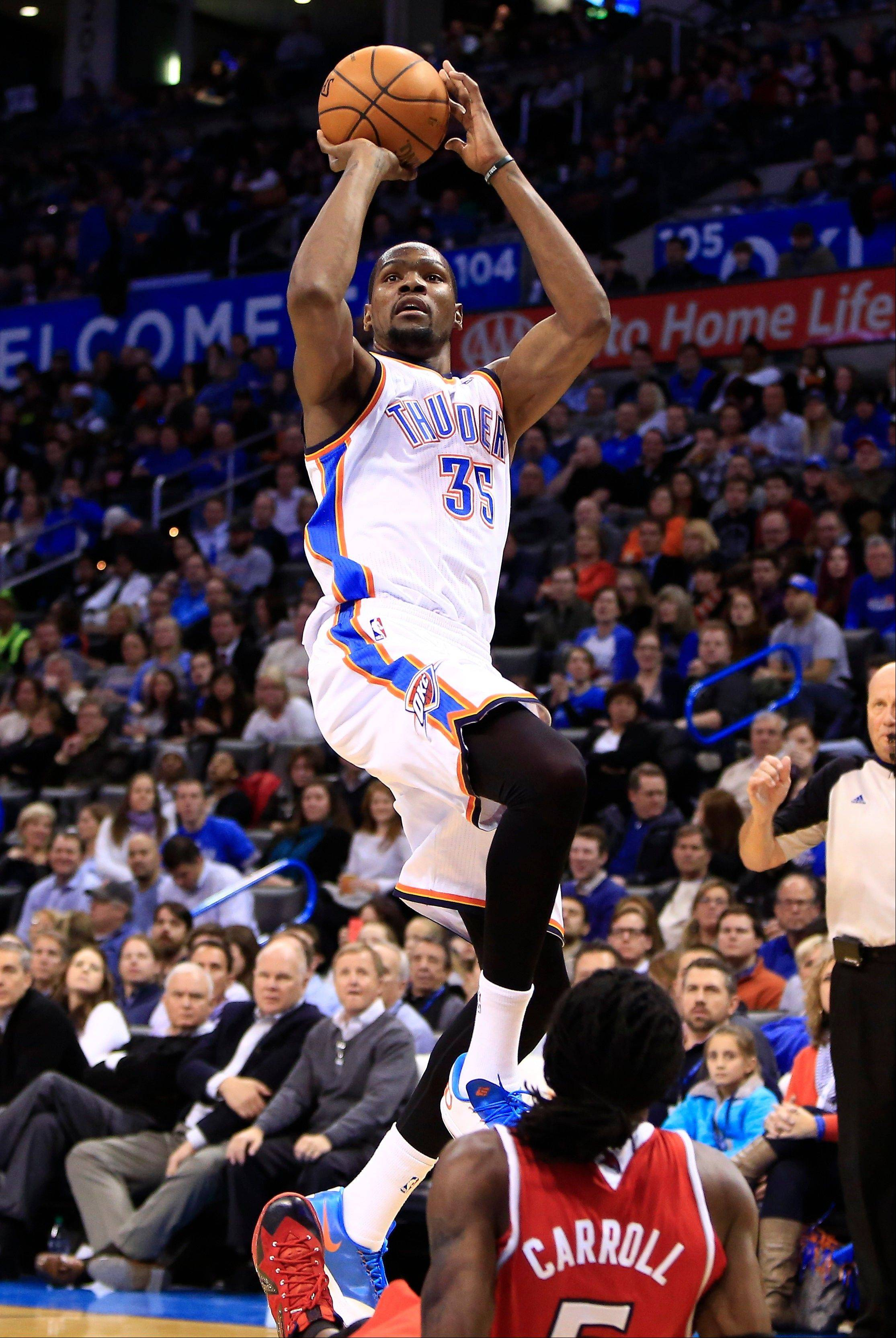 Oklahoma City Thunder forward Kevin Durant (35) shoots over Atlanta Hawks forward DeMarre Carroll during the fourth quarter of an NBA basketball game Monday in Oklahoma City. Oklahoma City won 111-109.