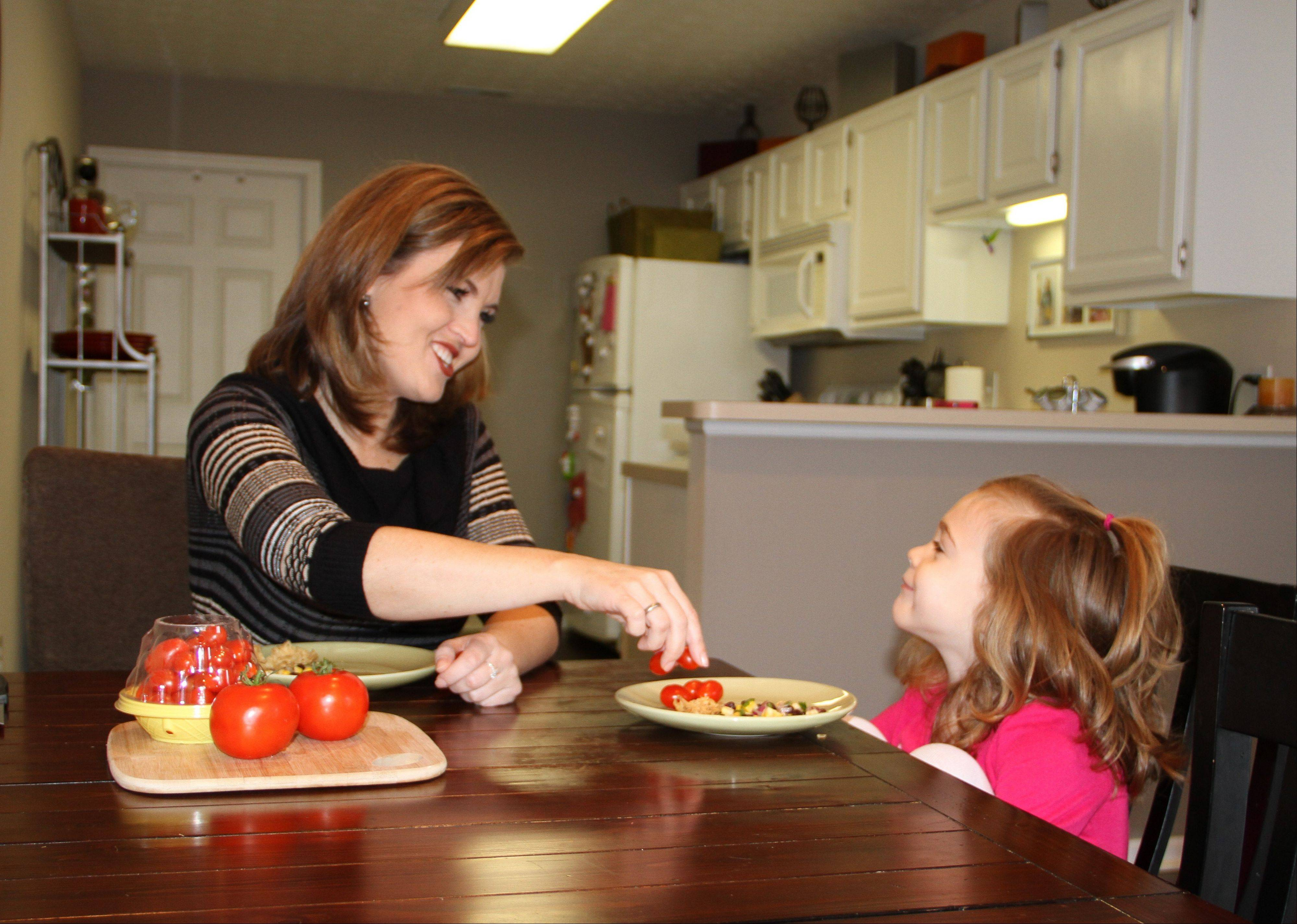 Shannon McCormick, left, serves a tomato to her 4-year-old daughter Sophie Chapman at their home in Gahanna, Ohio. Although not fond of tomatoes, McCormick keeps that fact from her daughter, who loves them.