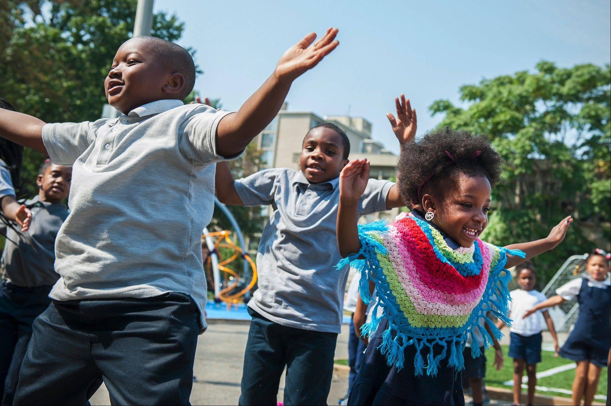 Johntae McFarland, Terrance Turner and Zanniyah Freeman do jumping jacks before recess at Amidon-Bowen Elementary School; studies show that recess not only improves children's fitness, but benefits their emotional growth and academic performance.