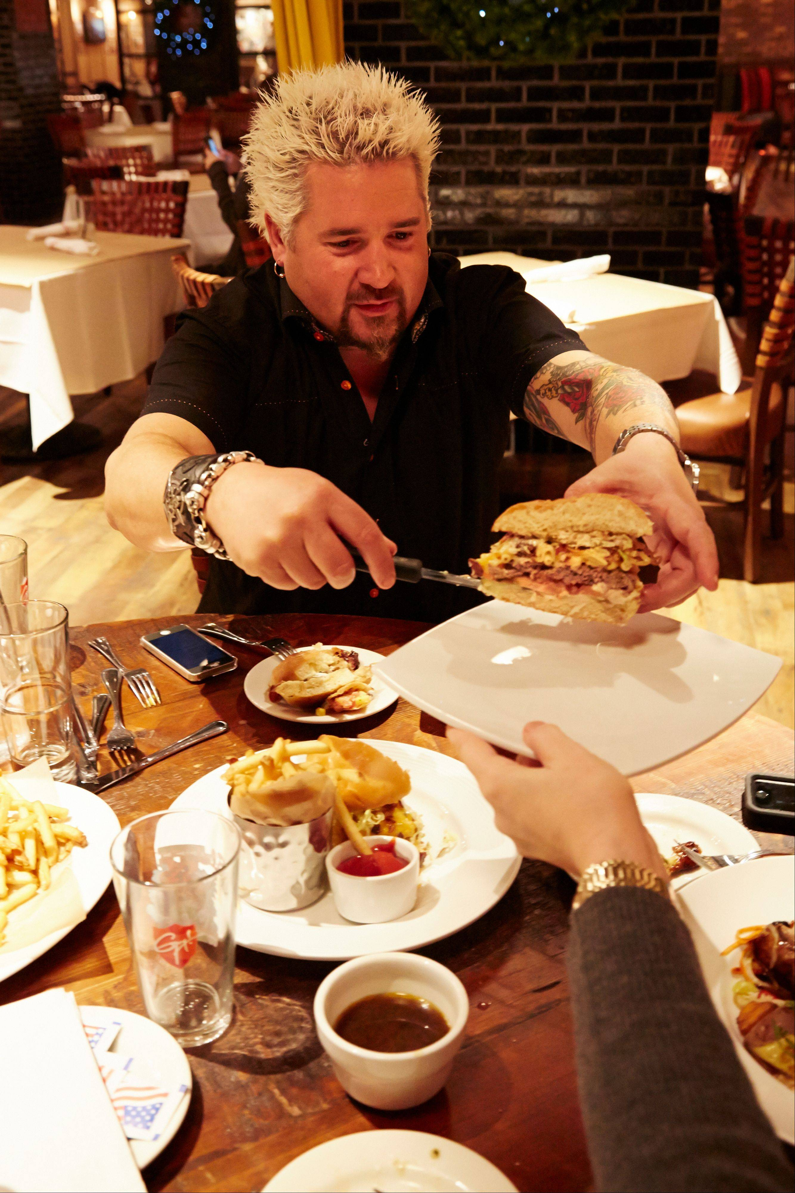Guy Fieri places a slice of the mac and cheese burger on a plate for comedian Judy Gold at Guy's American Kitchen and Bar during a tour of premier places to get Super Bowl grub in New York.