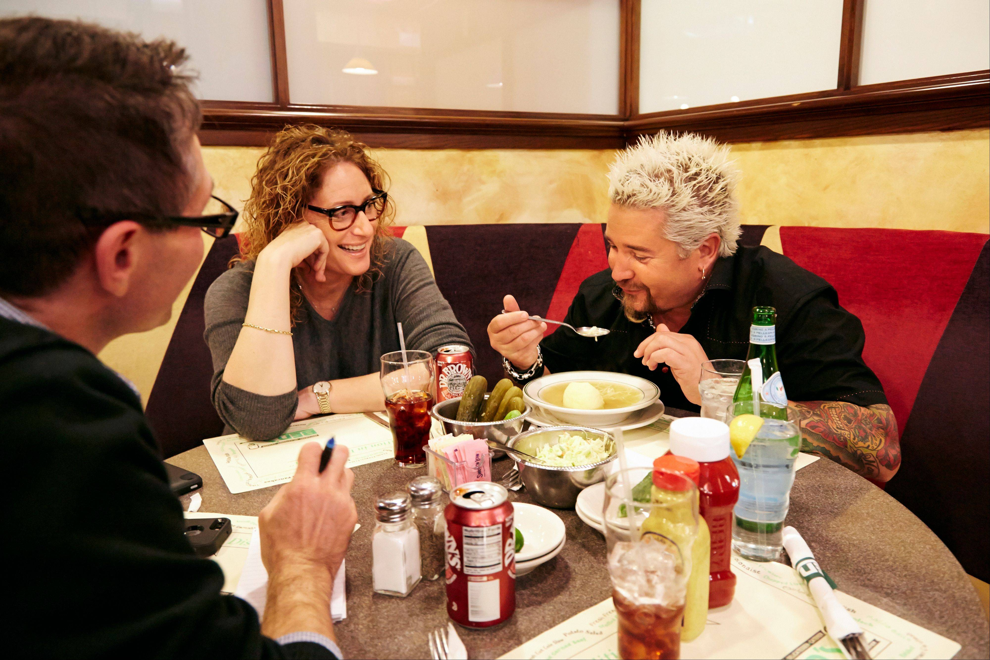 Food Network star Guy Fieri, right, tastes matzo ball soup at Ben's Deli as comedian Judy Gold, center, and Associated Press food editor J.M Hirsh joined the pair on a tour of premier places to get Super Bowl grub in New York.