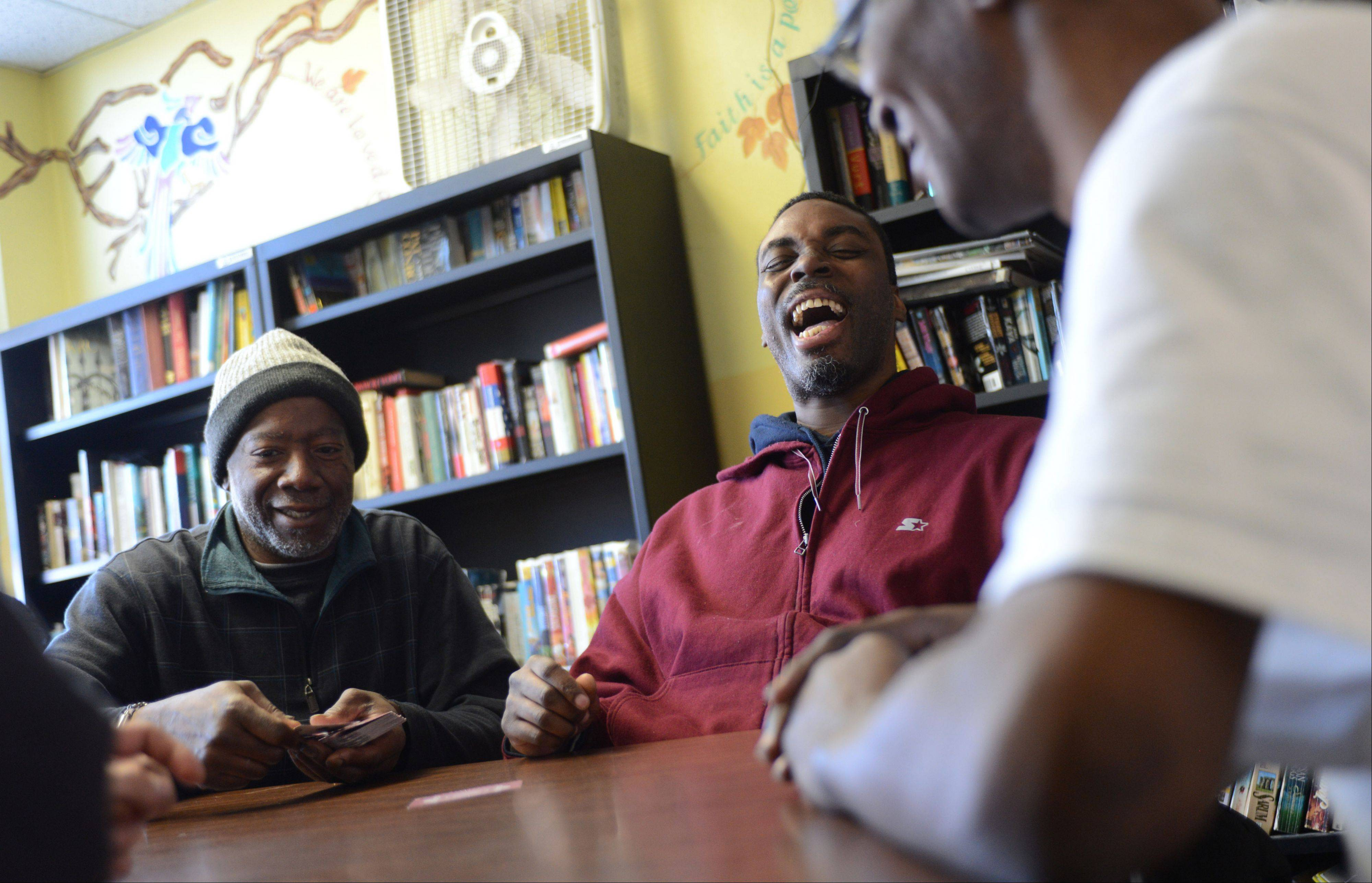 PADS guests James Banks Jr., left, Jerome Bishop and Christopher Thompson share a laugh while playing cards and keeping warm Monday morning at the shelter in North Chicago.