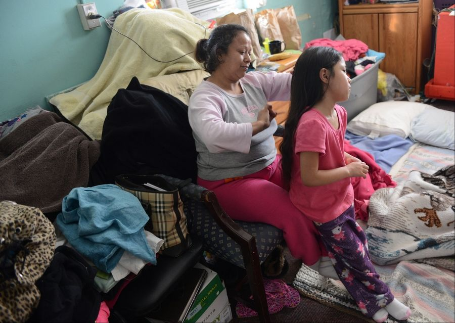 Tsi-Tsi-Ki Dominguez, 7, has her hair combed by her mother, Julia Dominguez, Monday morning at the North Chicago PADS facility. The Dominguez family was sharing a space in the shelter with another family.