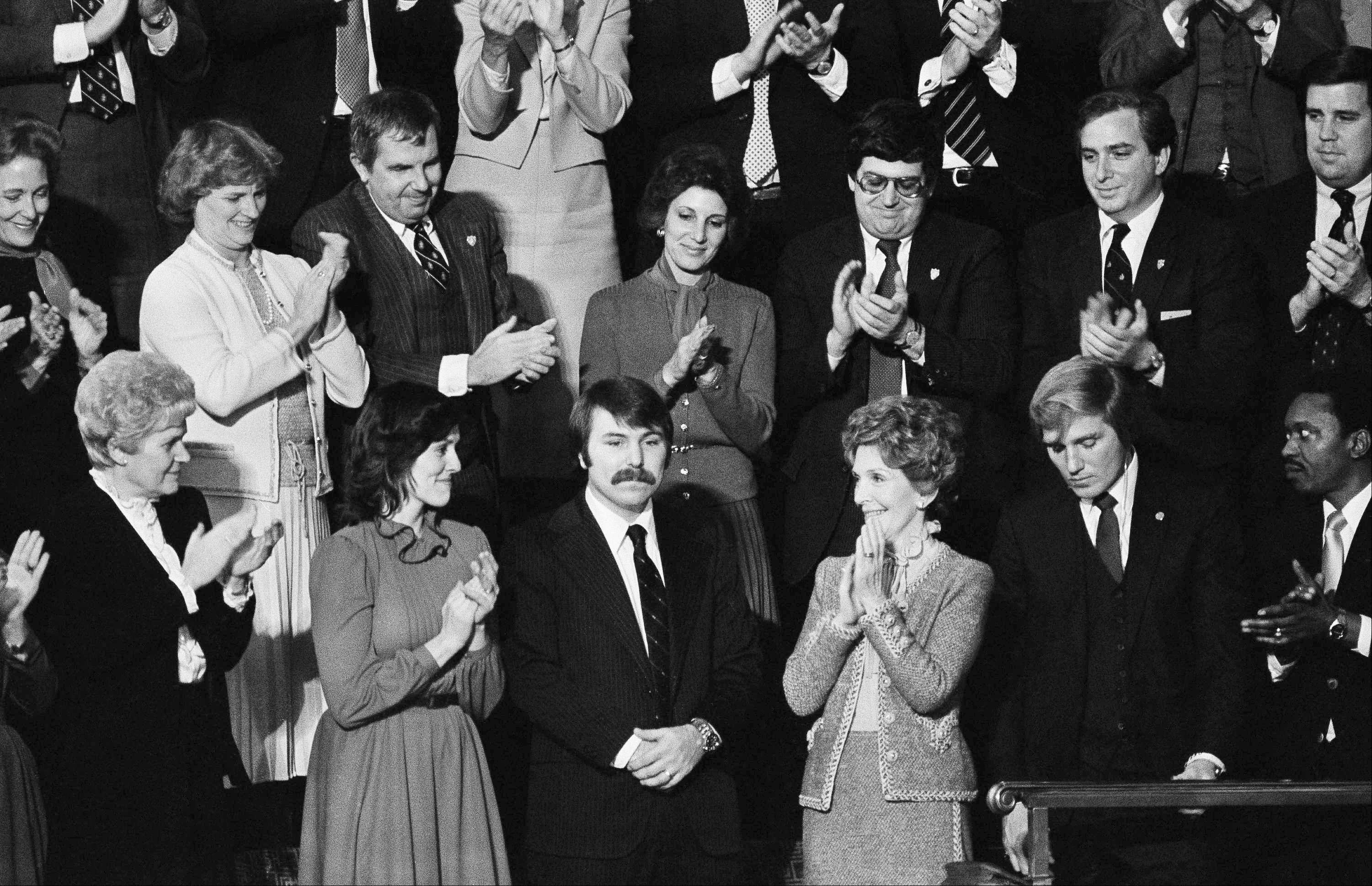 Lennie Skutnik, center front, the man who jumped into the Potomac River and saved one of the passengers aboard the Air Florida jetliner that crashed on Jan. 13, 1983, receives applause from first lady Nancy Reagan and his wife, second from left, after President Ronald Reagan made mention of the event in his State of the Union address Jan. 27, 1982.