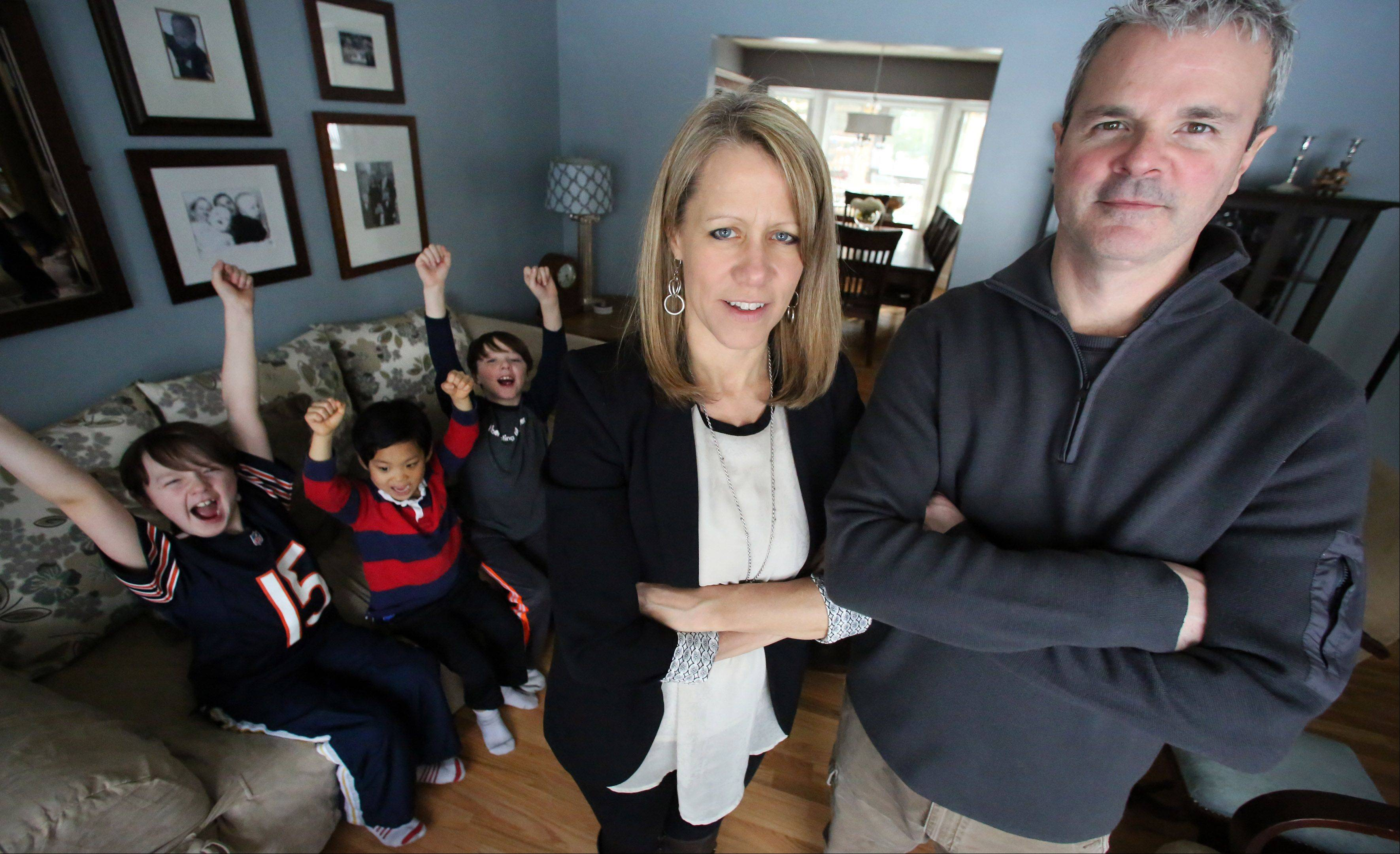 Jen and Will Ortman at their home in Arlington Heights just found out before this photo was taken on Sunday that their son's Nick, 9, left to right, Nate, 5, and Max, 9, will be staying home on Monday and Tuesday due to school closures.