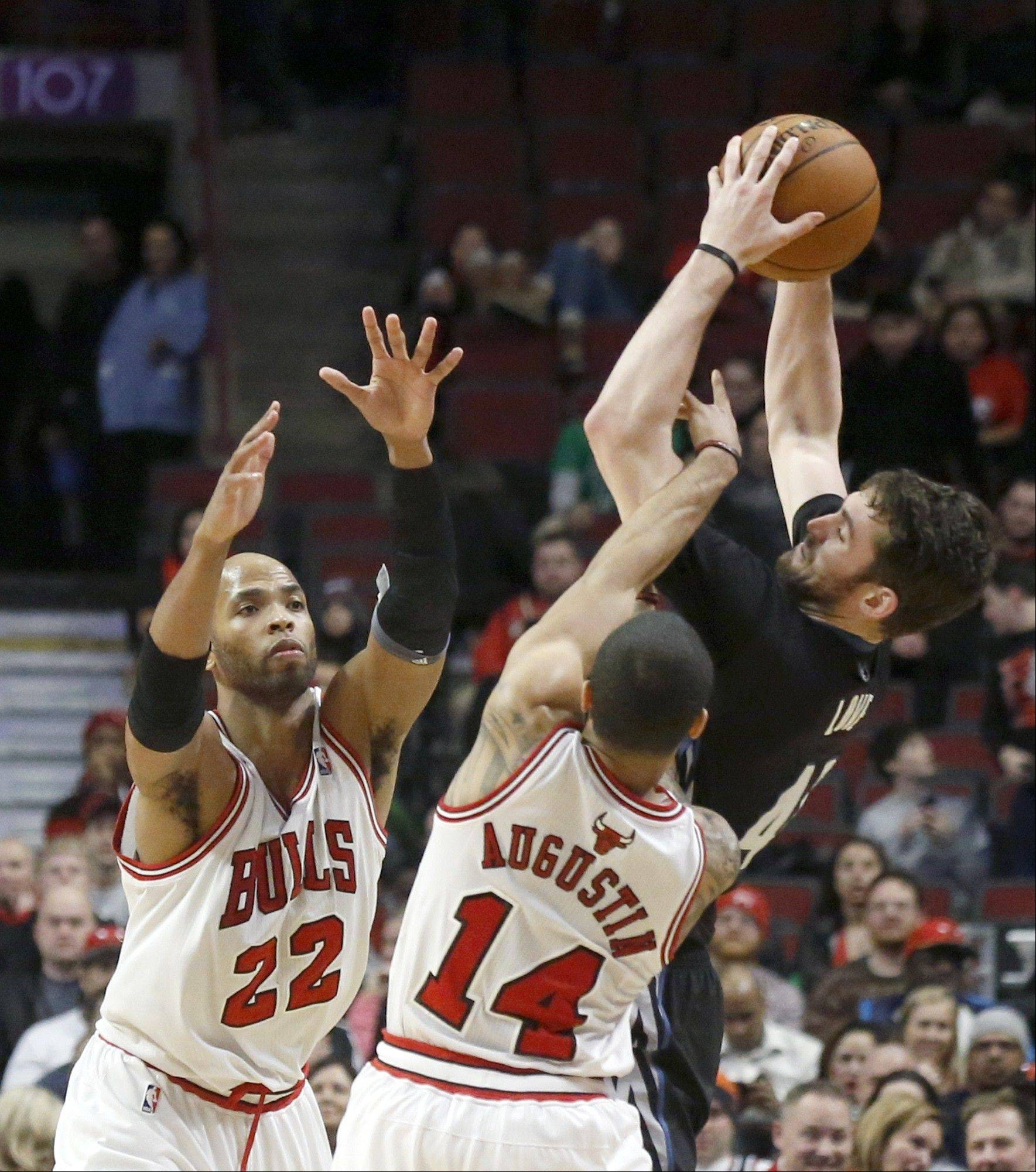 The Timberwolves' Kevin Love is fouled by Bulls guard D.J. Augustin as Taj Gibson also defends during the second half Monday night. Love finished with 31 points.